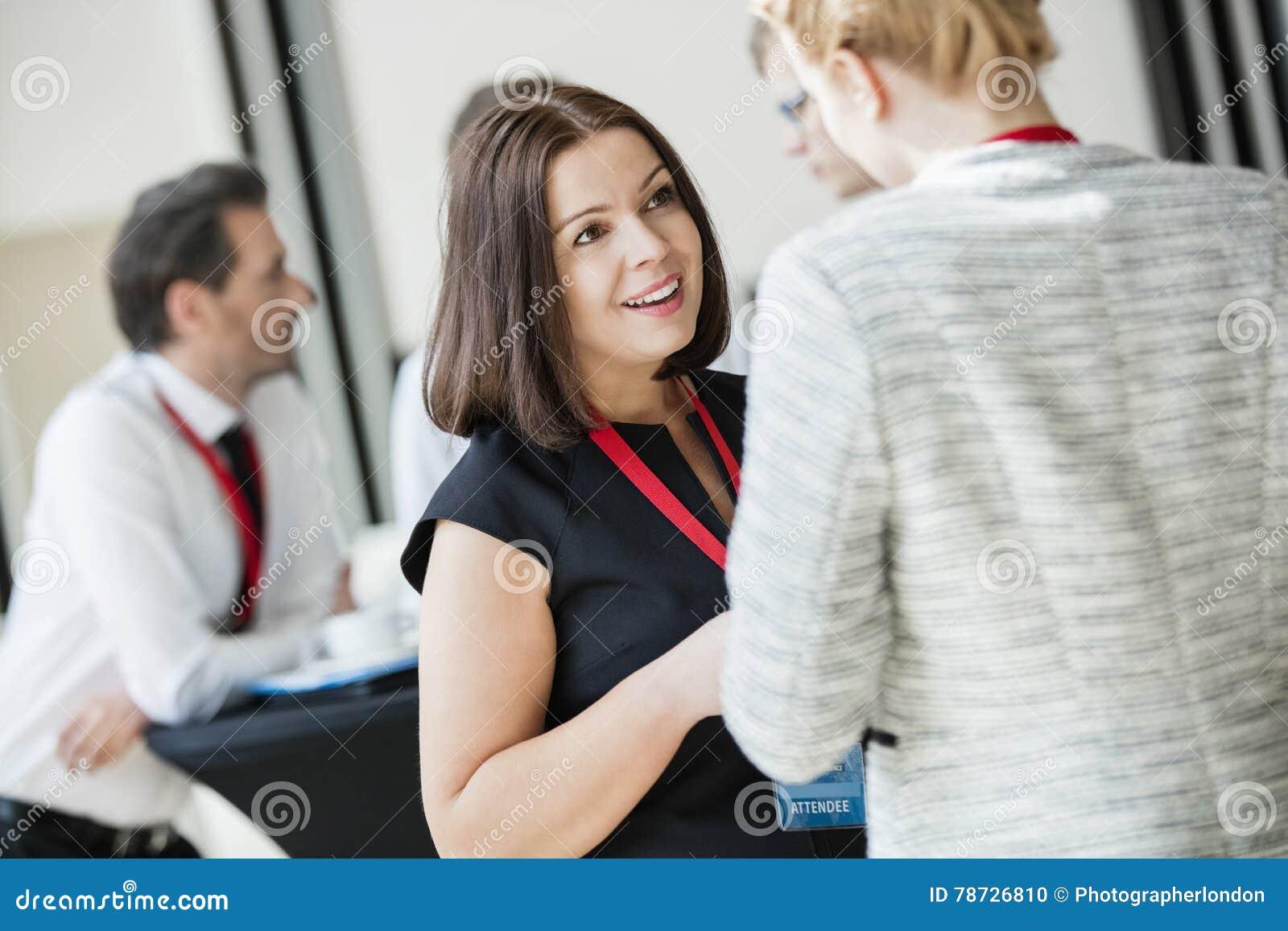 Affärskvinnor som talar under kaffeavbrott på konventcentret