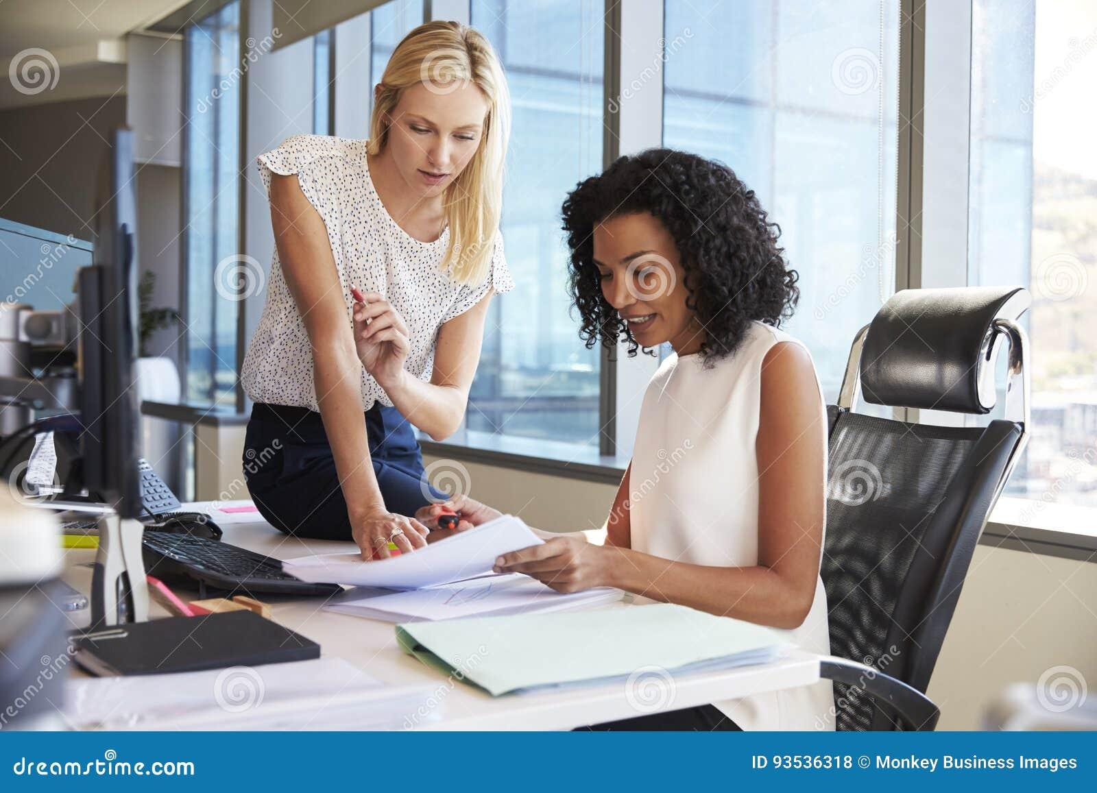 Affärskvinnor som tillsammans arbetar på kontorsskrivbordet på datoren