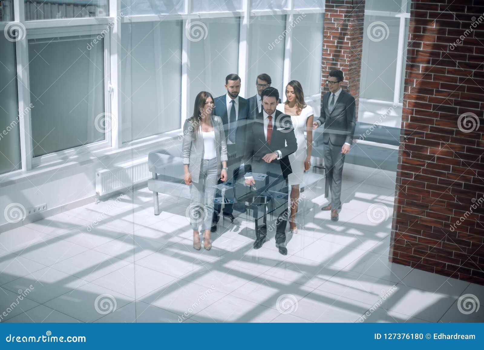 Affärslaget, businesspeople grupperar att gå på den moderna ljusa kontorsinre