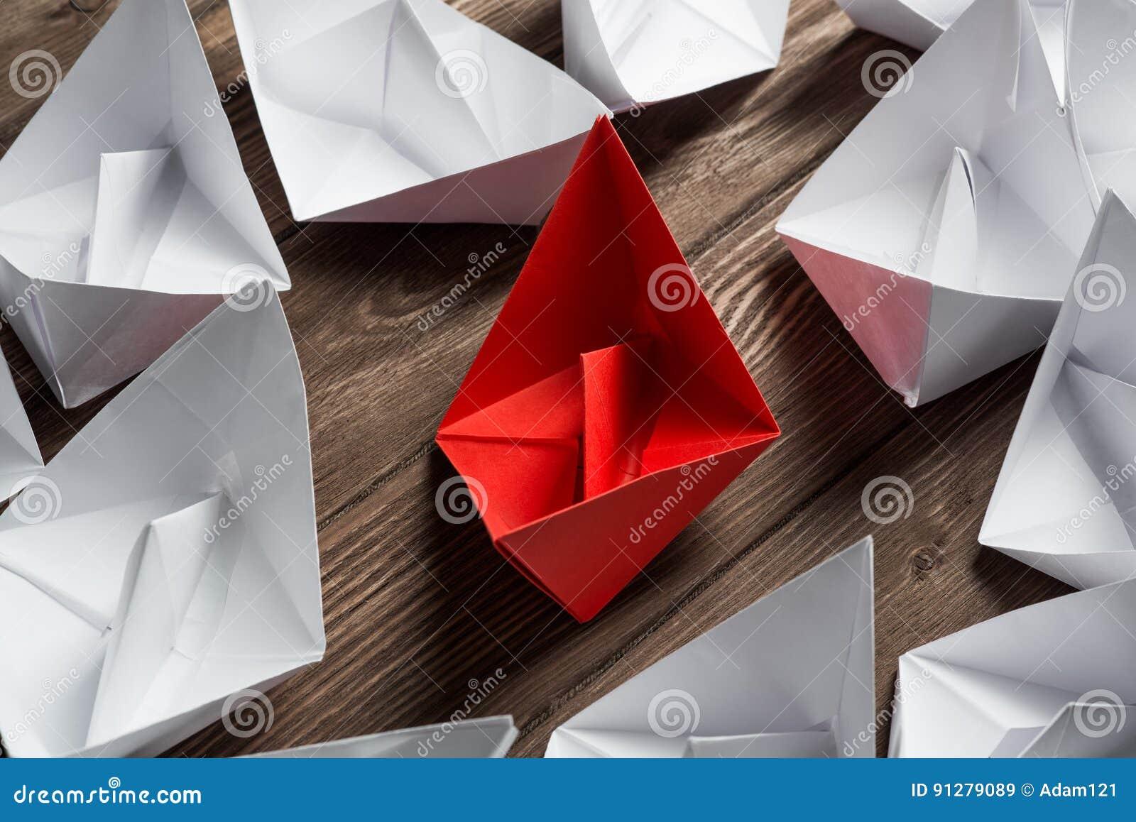 Affärsledarskapbegrepp med pappers- fartyg för vit och för färg på trätabellen