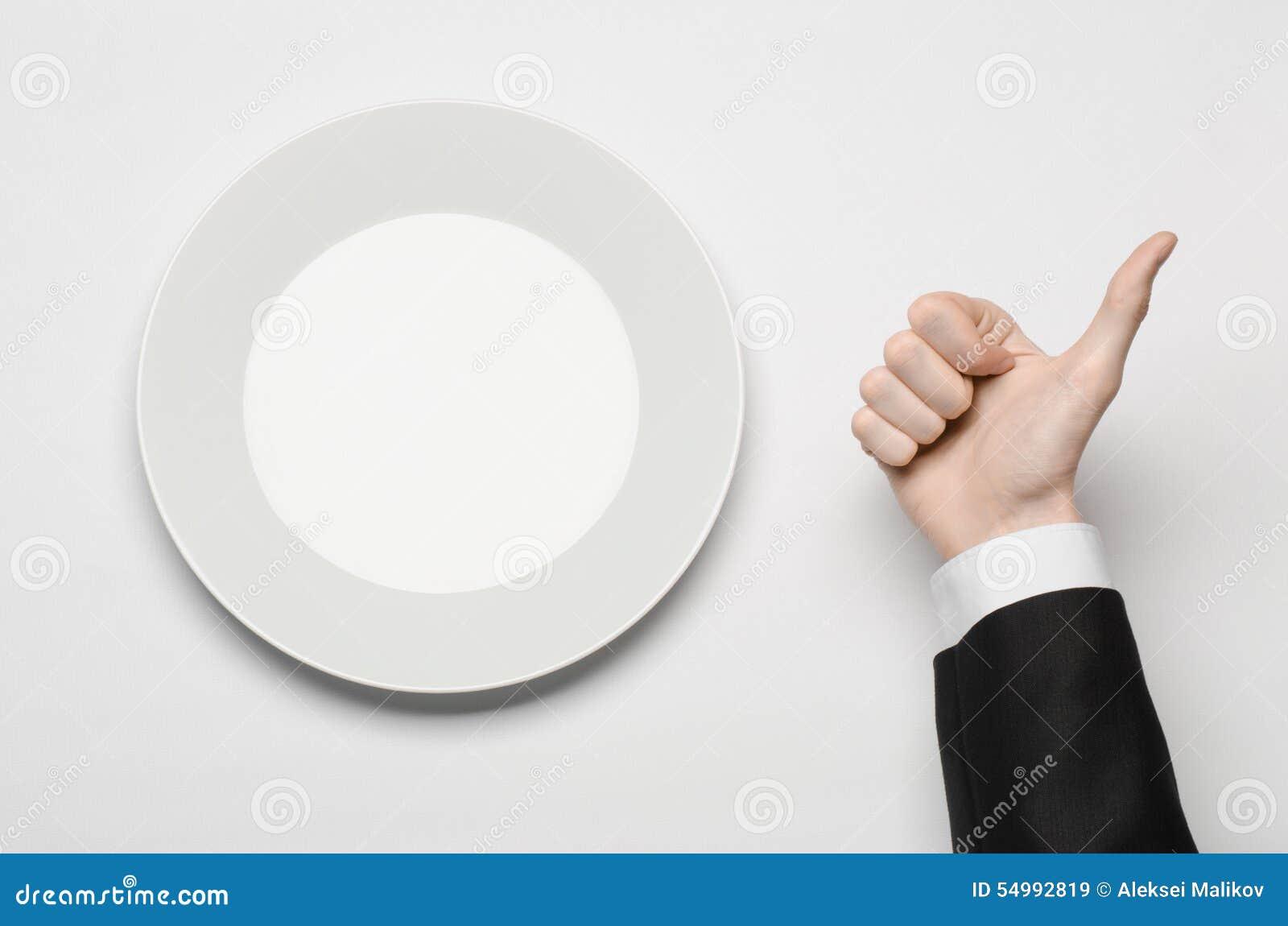 Affärslunch och sunt mattema: mannens hand i en svart dräkt som rymmer ett vitt, tömmer plattan, och shower fingrar gest på en is