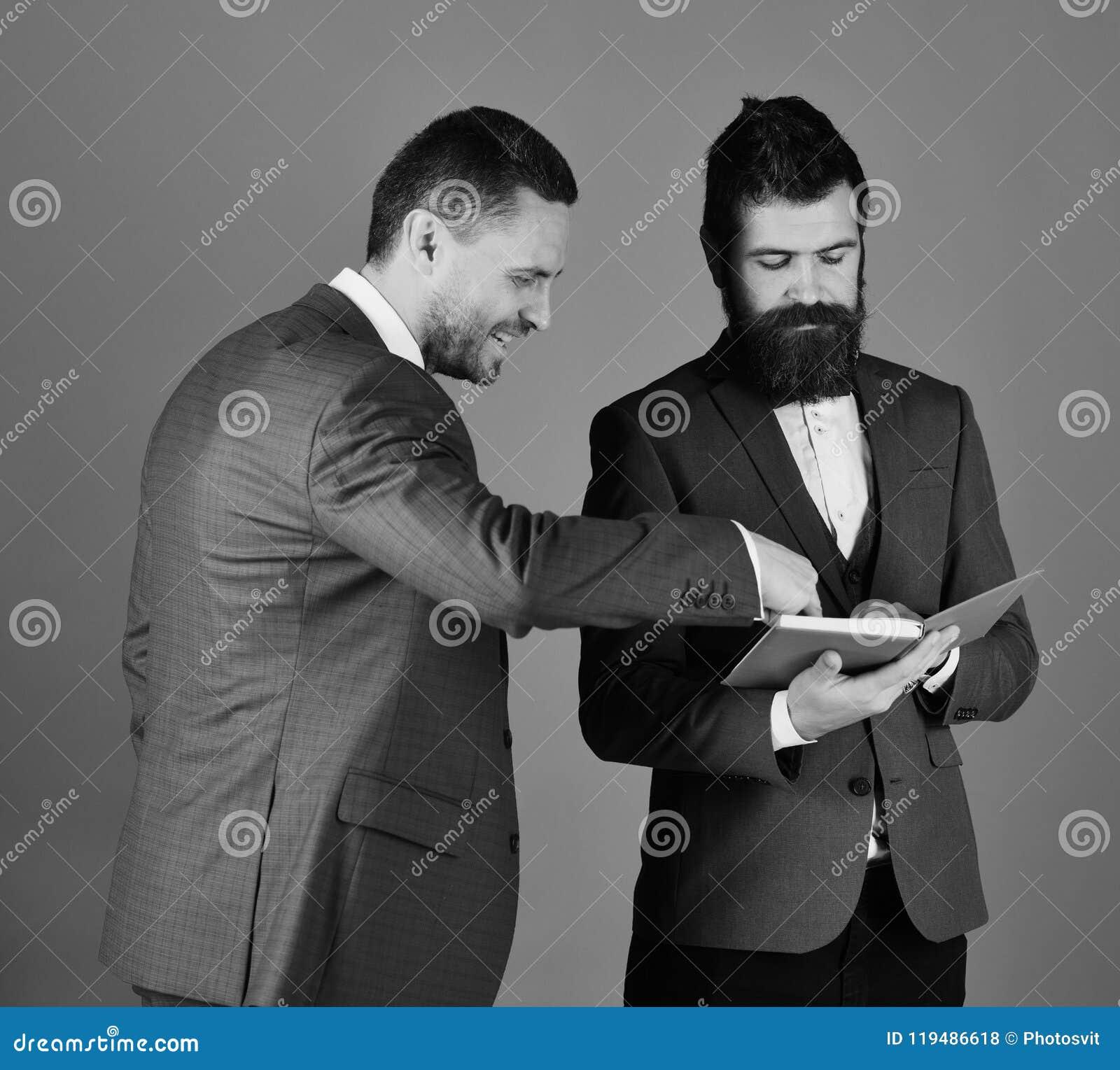 Affärsmän med skägg diskuterar affären som ser in i anmärkningar Machos i klassiskt dräktsamtal om schema Män med