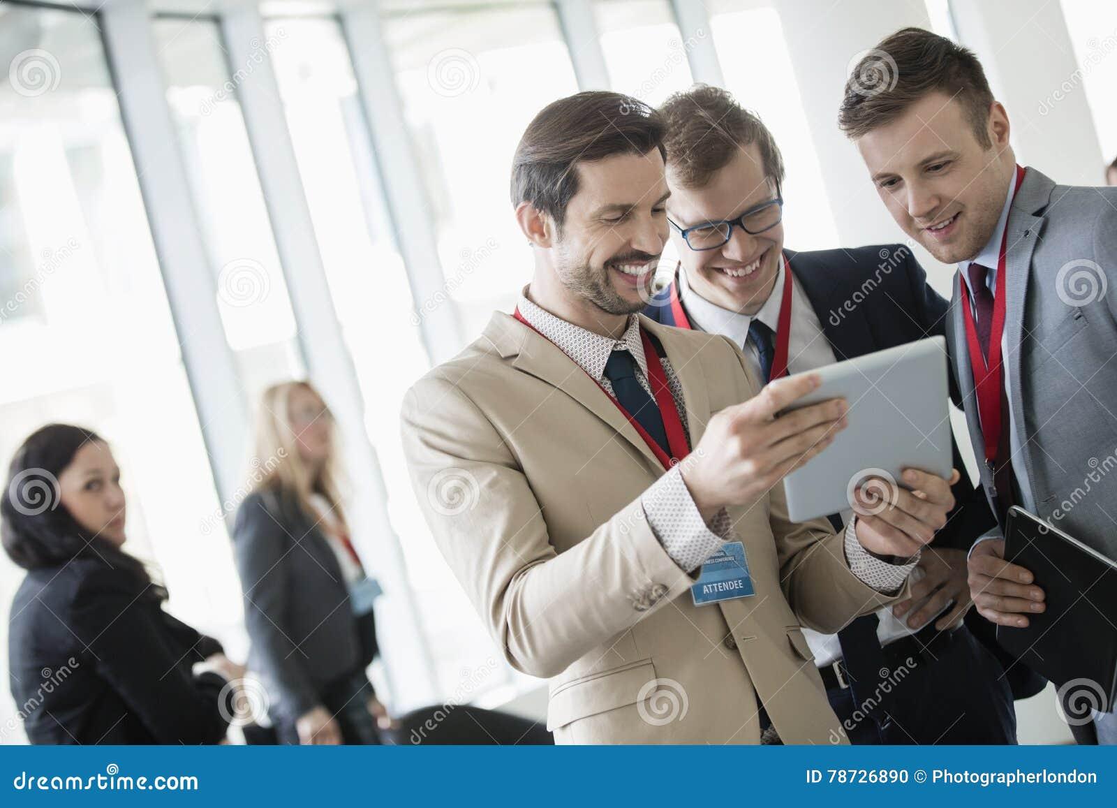 Affärsmän som använder den digitala minnestavlan på konventcentret