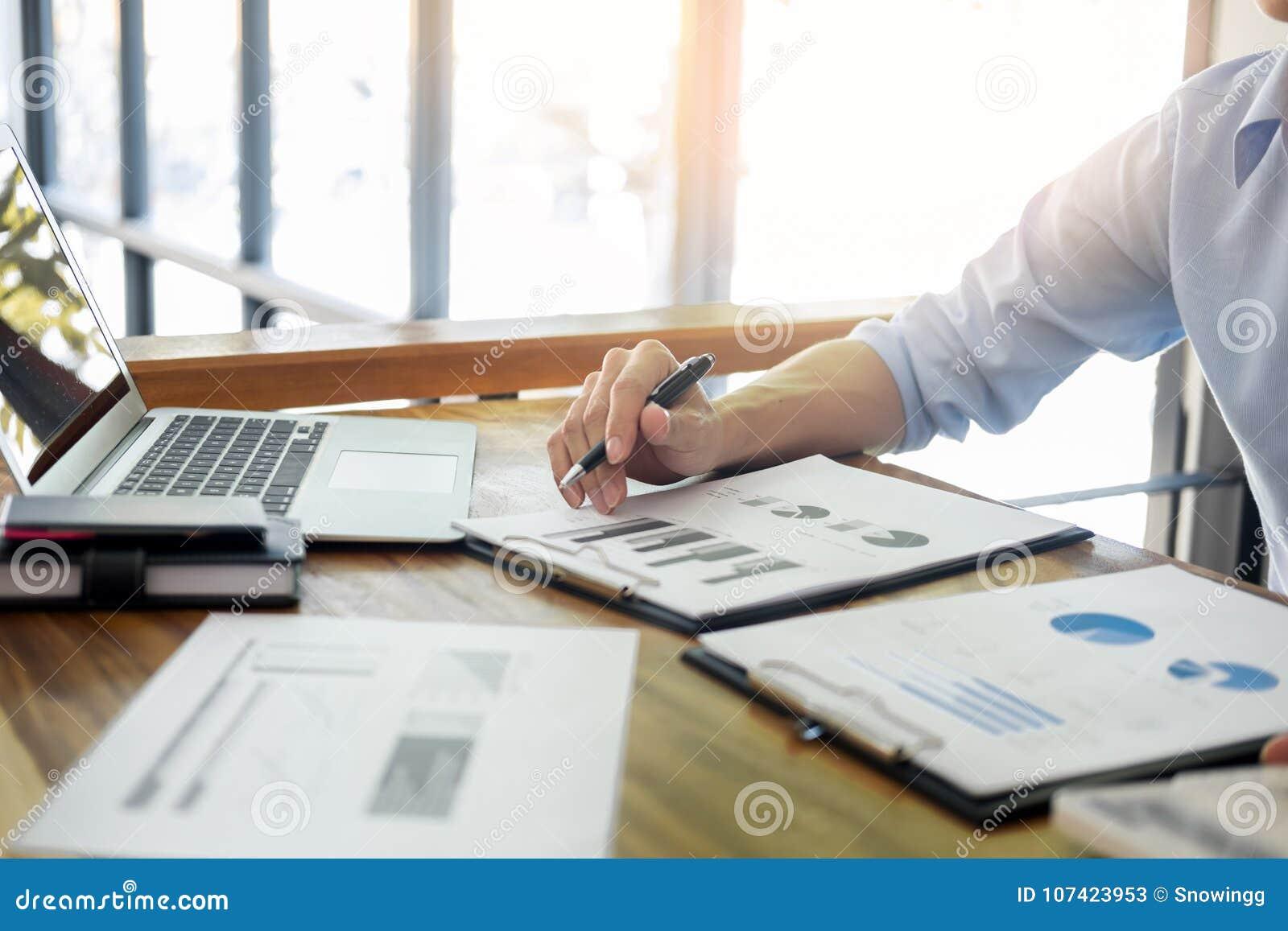 Affärsmän som arbetar på trädesk& x28; table& x29; med anteckningsbokcompute