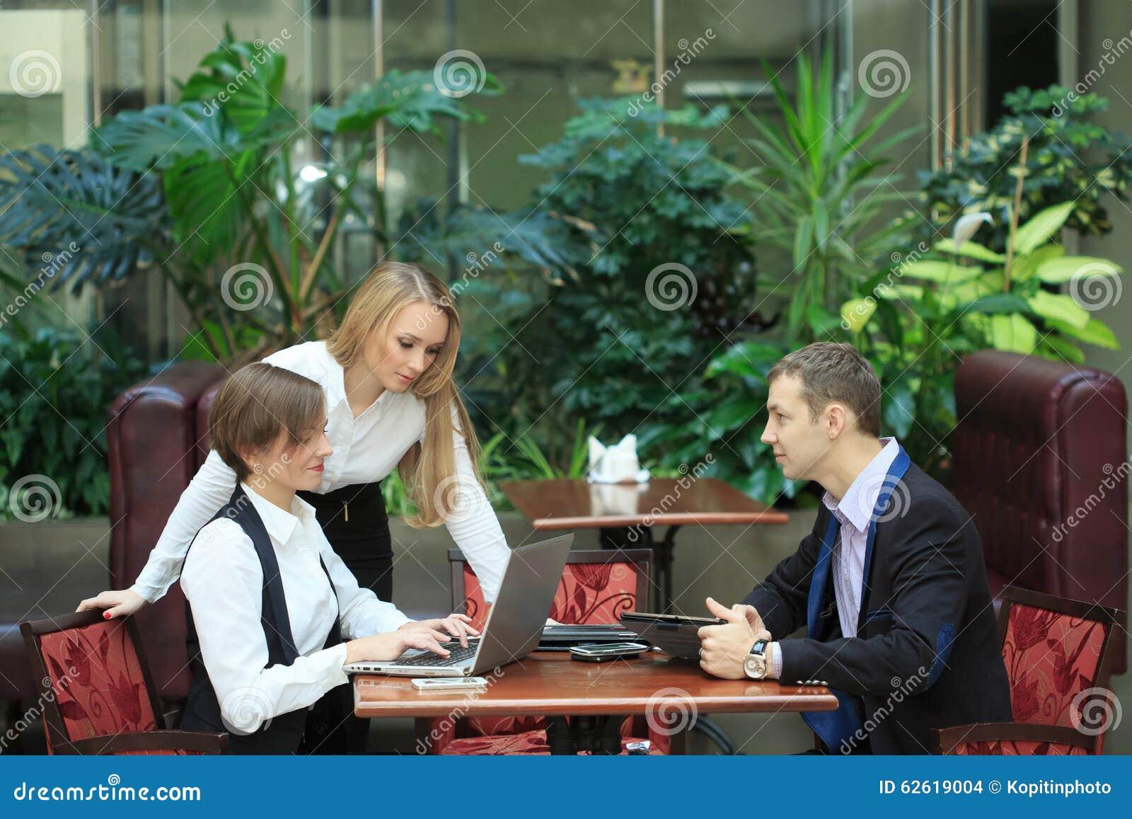 Affärsmän som sitter i kafét för en bärbar dator