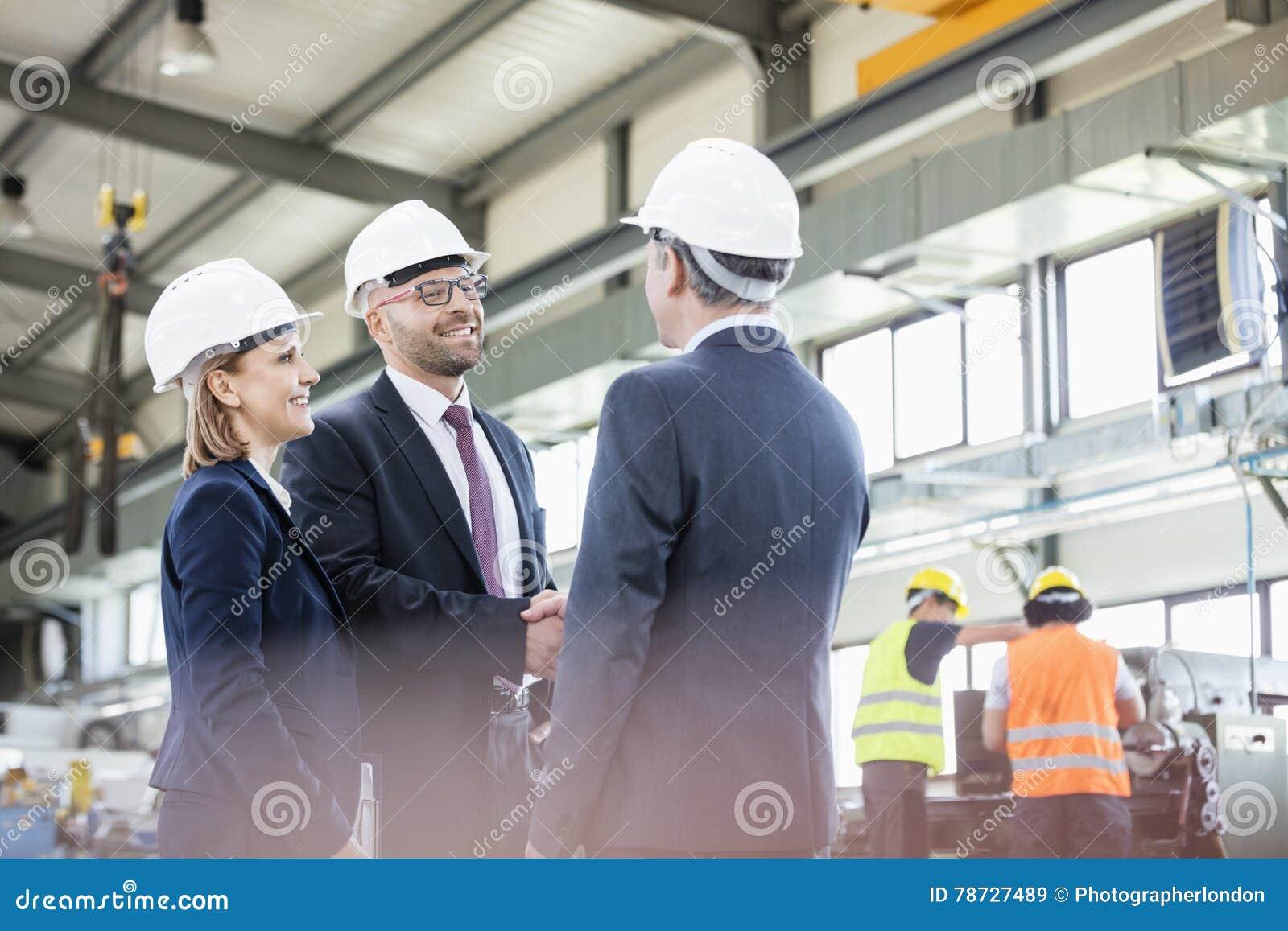 Affärsmän som skakar händer med arbetare som arbetar i bakgrund på metallbransch
