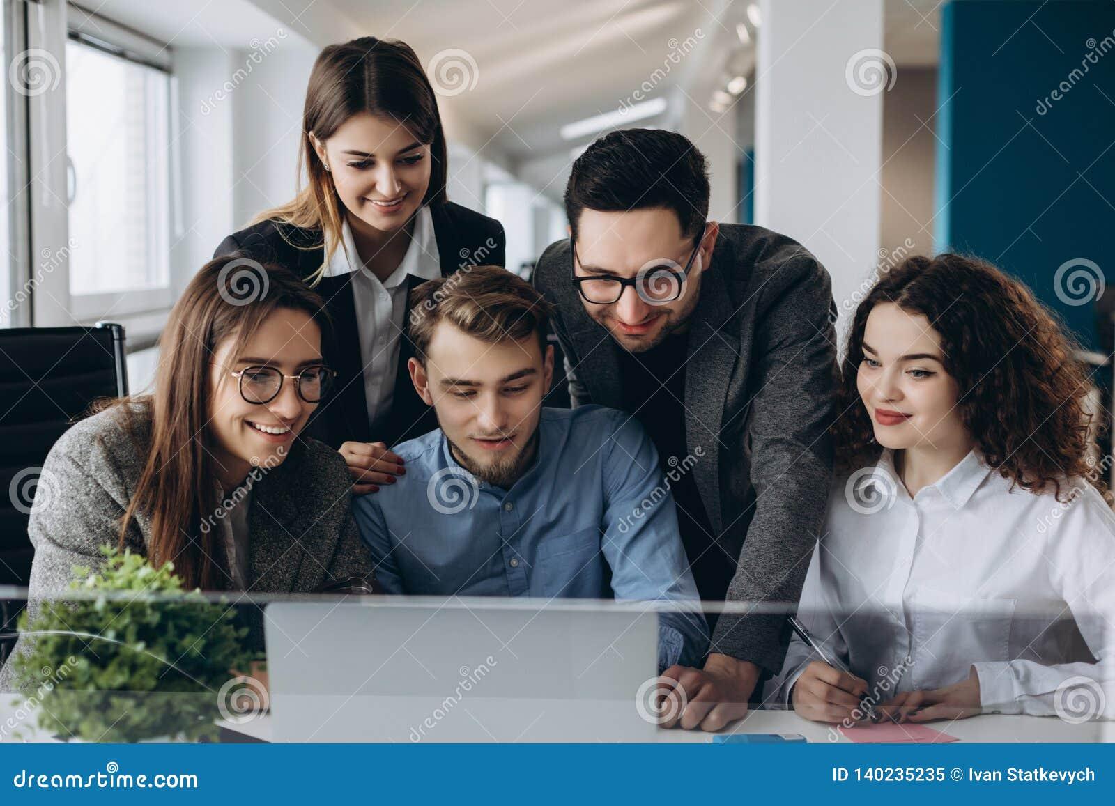 Affärsmöte, ungt coworkerlag som gör stor affärsdiskussion med datoren i Co-arbete kontor Teamworkfolkbegrepp