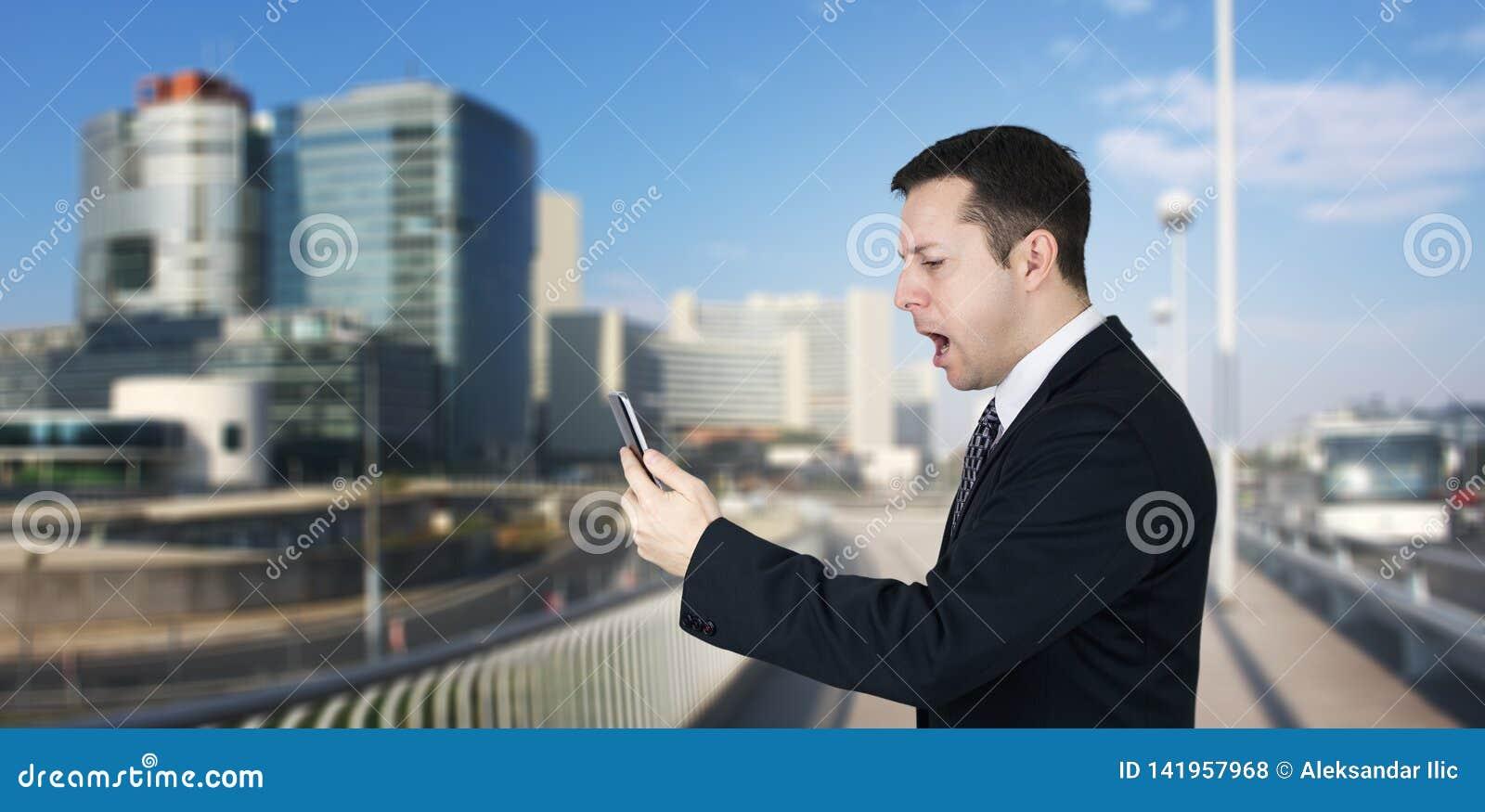 Affärsman Holding Smartphone i handen och känsla som är ilskna med affärsstaden och företags byggnader i bakgrund