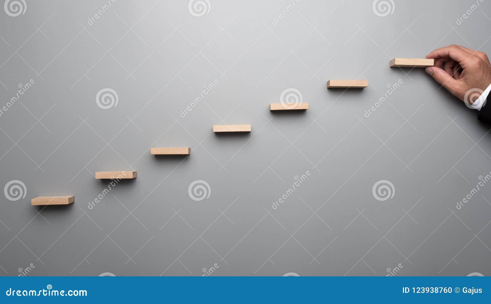 Affärsman i affärsdräkten som bygger en graf eller en stege av succe