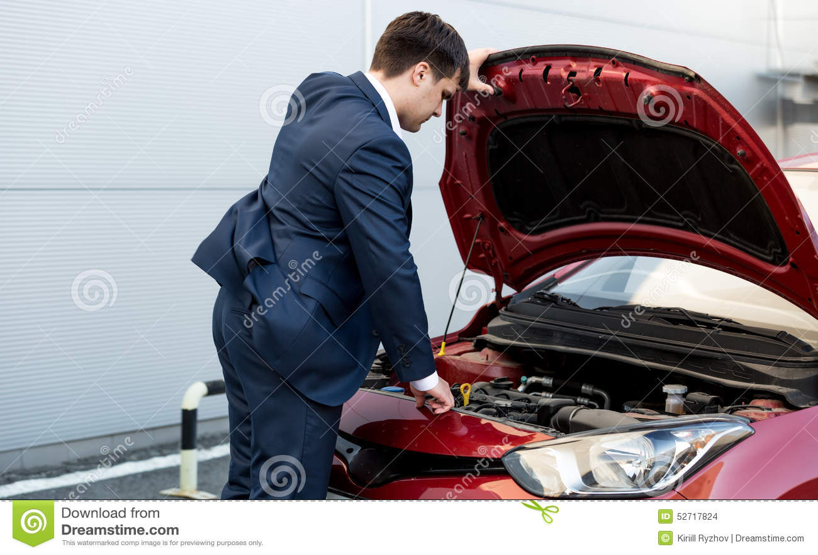 Affärsman i dräktöppningshätta av den öppna bilen