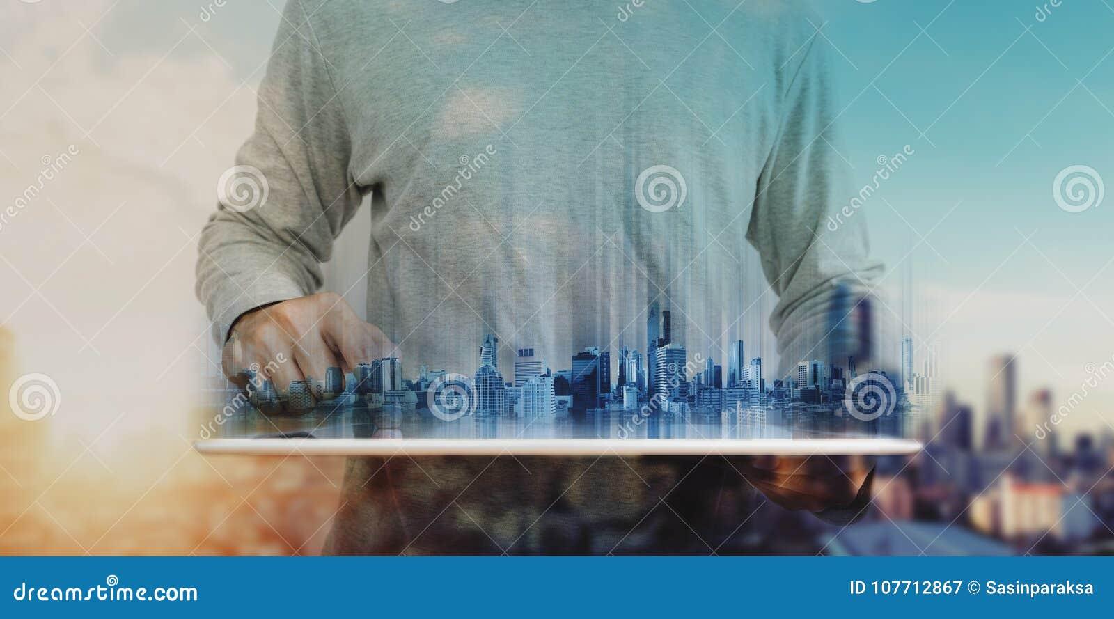 Affärsman i tillfälliga kläder genom att använda den digitala minnestavlan, med futuristiska moderna byggnader för hologram Fasti