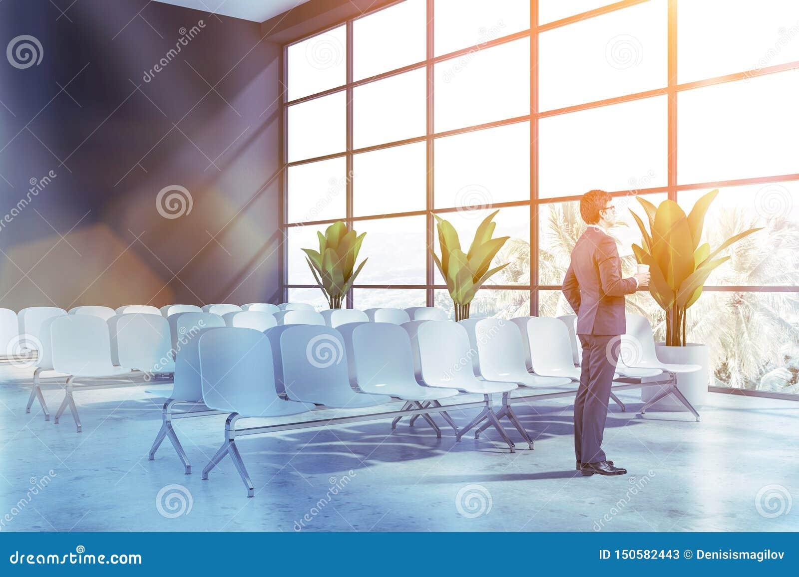 Affärsman i väntande rum för grå flygplats