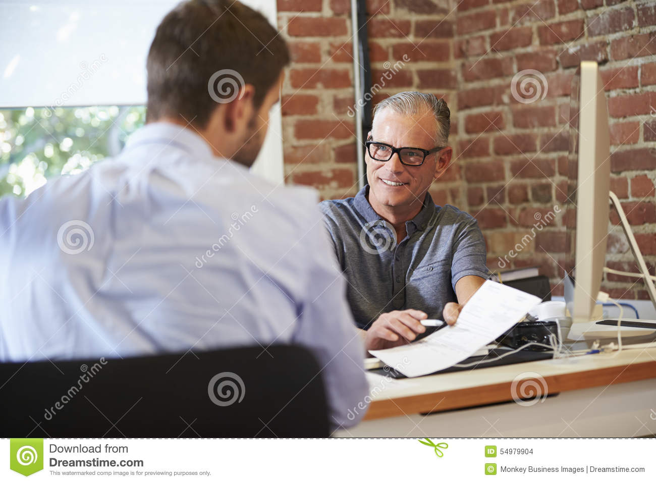 Affärsman Interviewing Male Job Applicant In Office