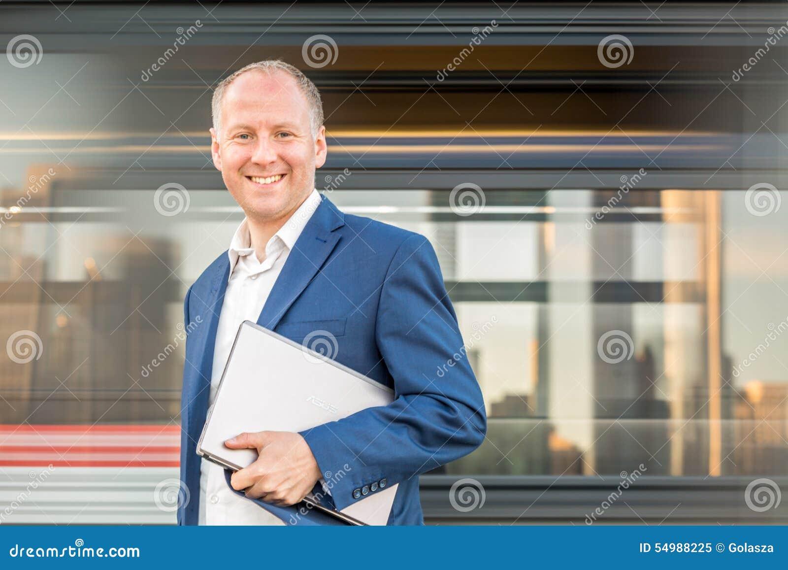 Affärsman med bärbara datorn på stads- bakgrund