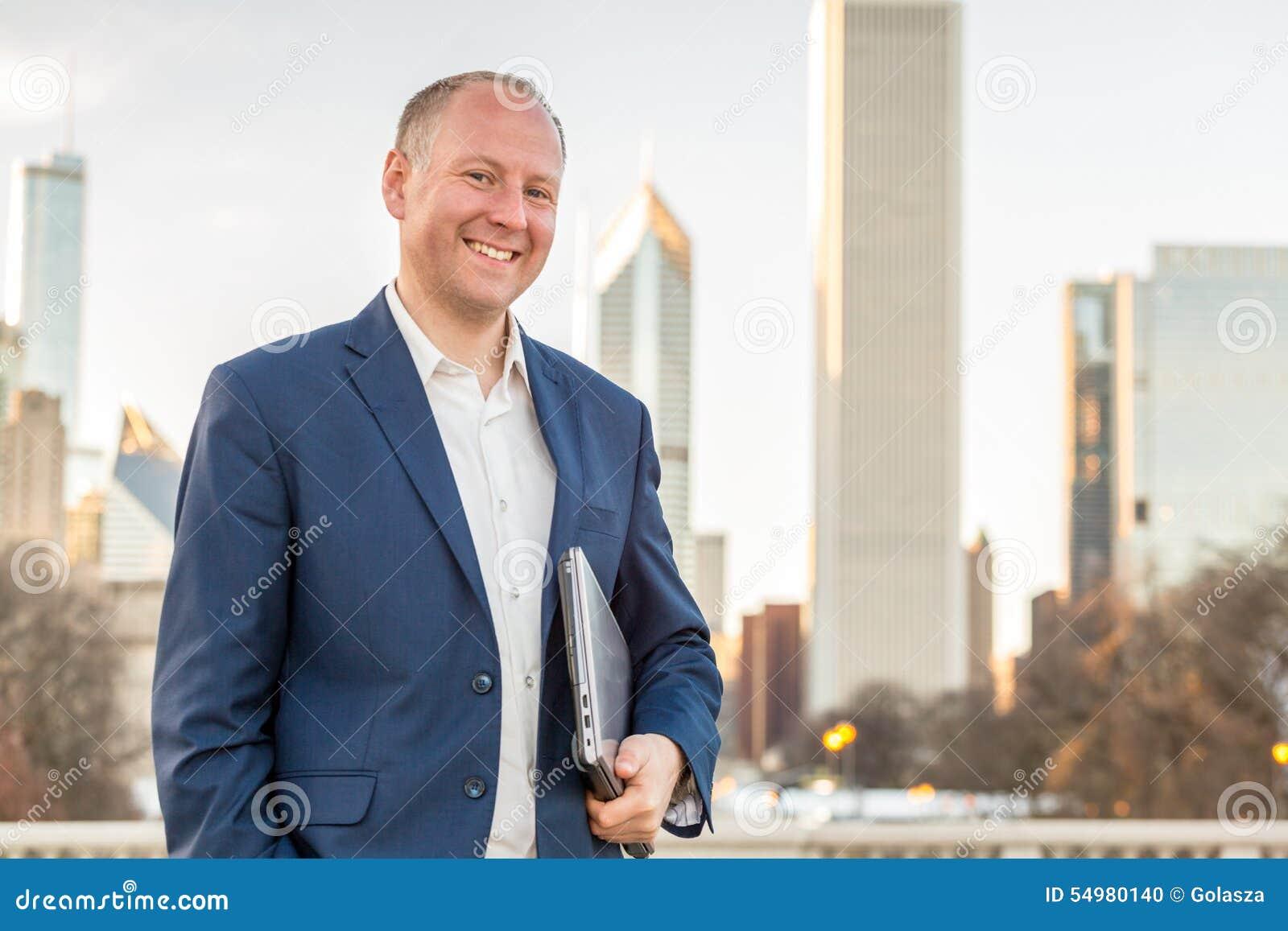 Affärsman med bärbara datorn som är främst av kontorsbyggnader