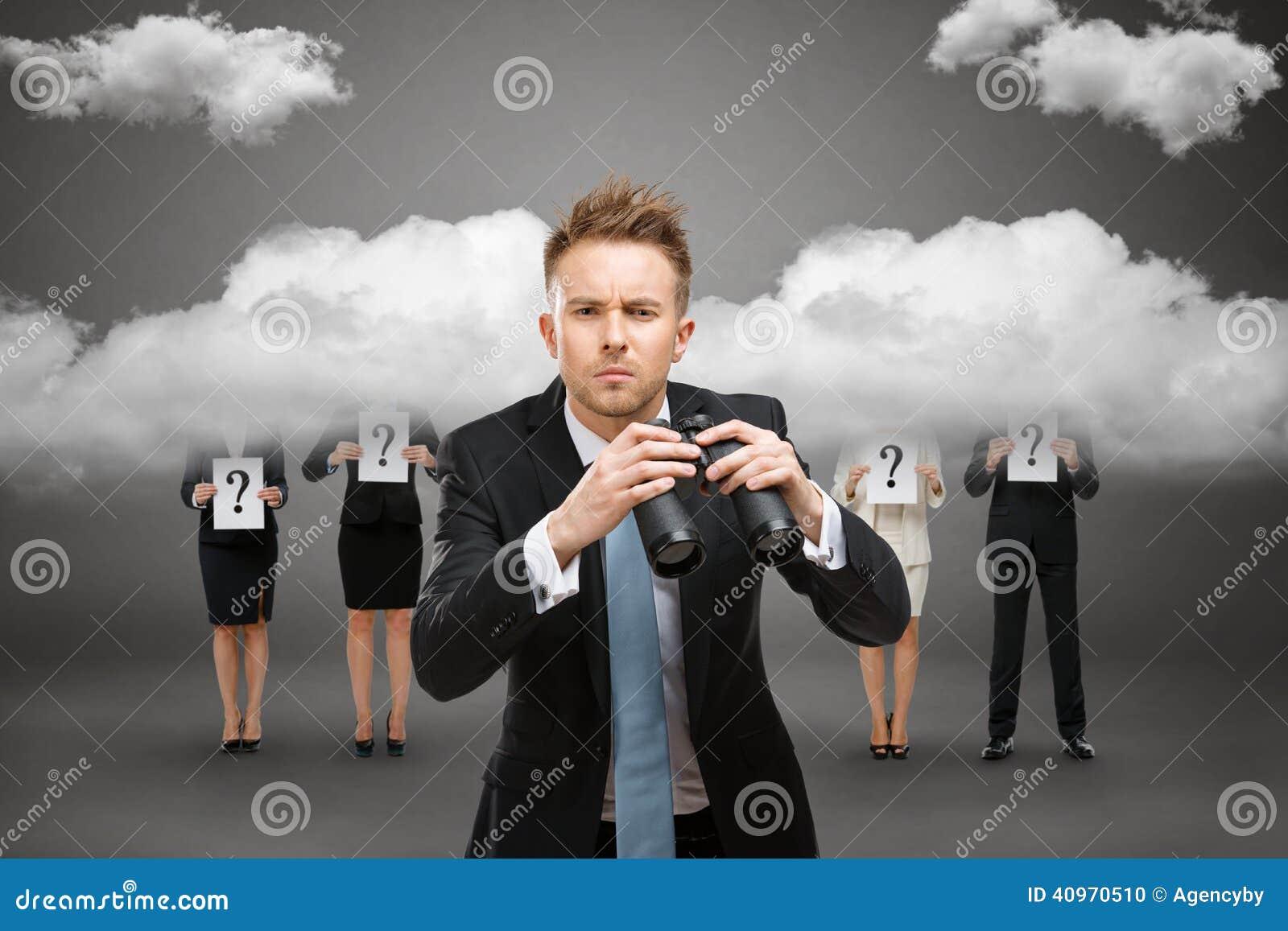 Affärsman med binokulärt mot stormig himmel