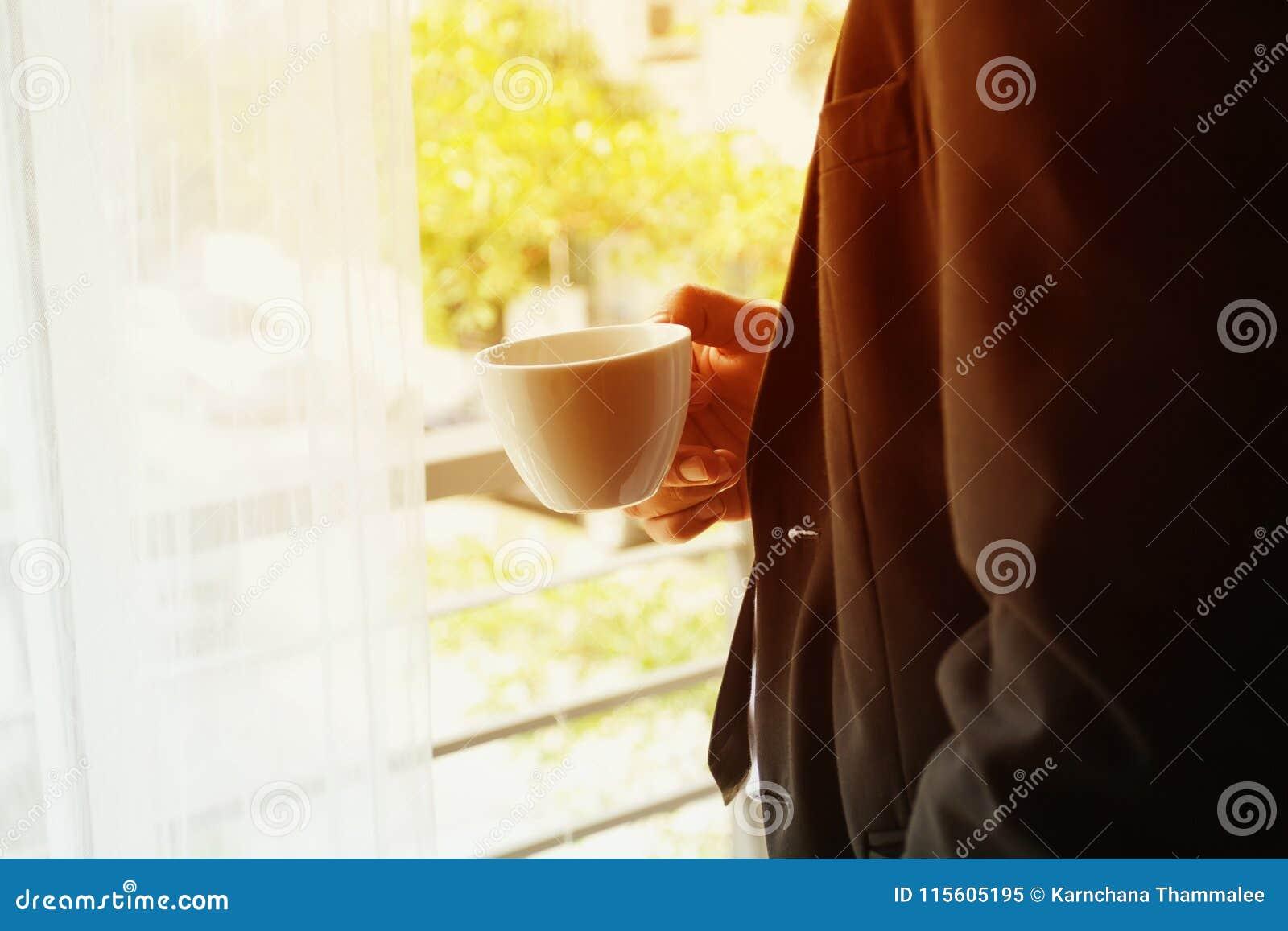 Affärsman med dräktställningen och den hållande kaffekoppen