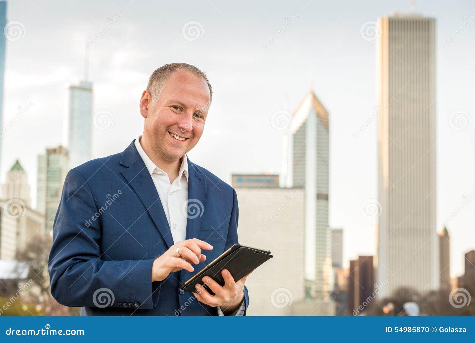 Affärsman med minnestavlan som är främst av kontorsbyggnader
