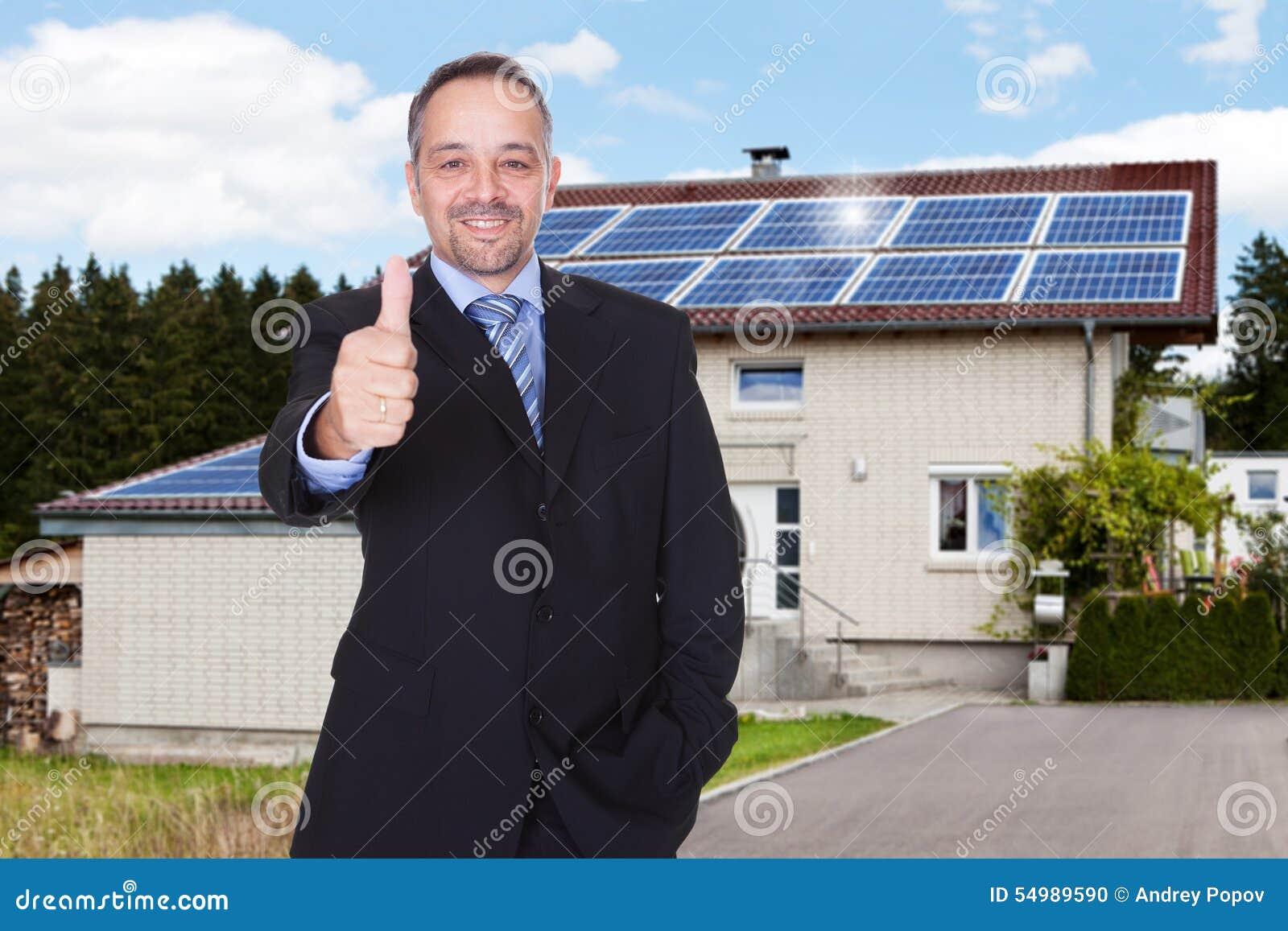 Affärsman med tummar upp framme av huset