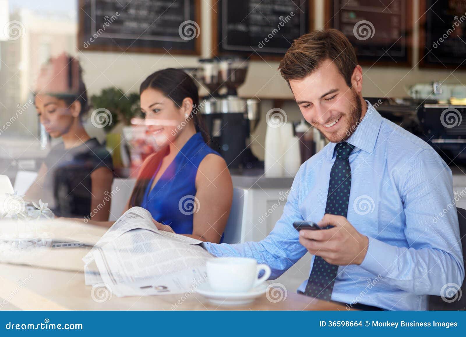Affärsman With Mobile Phone och tidning i coffee shop