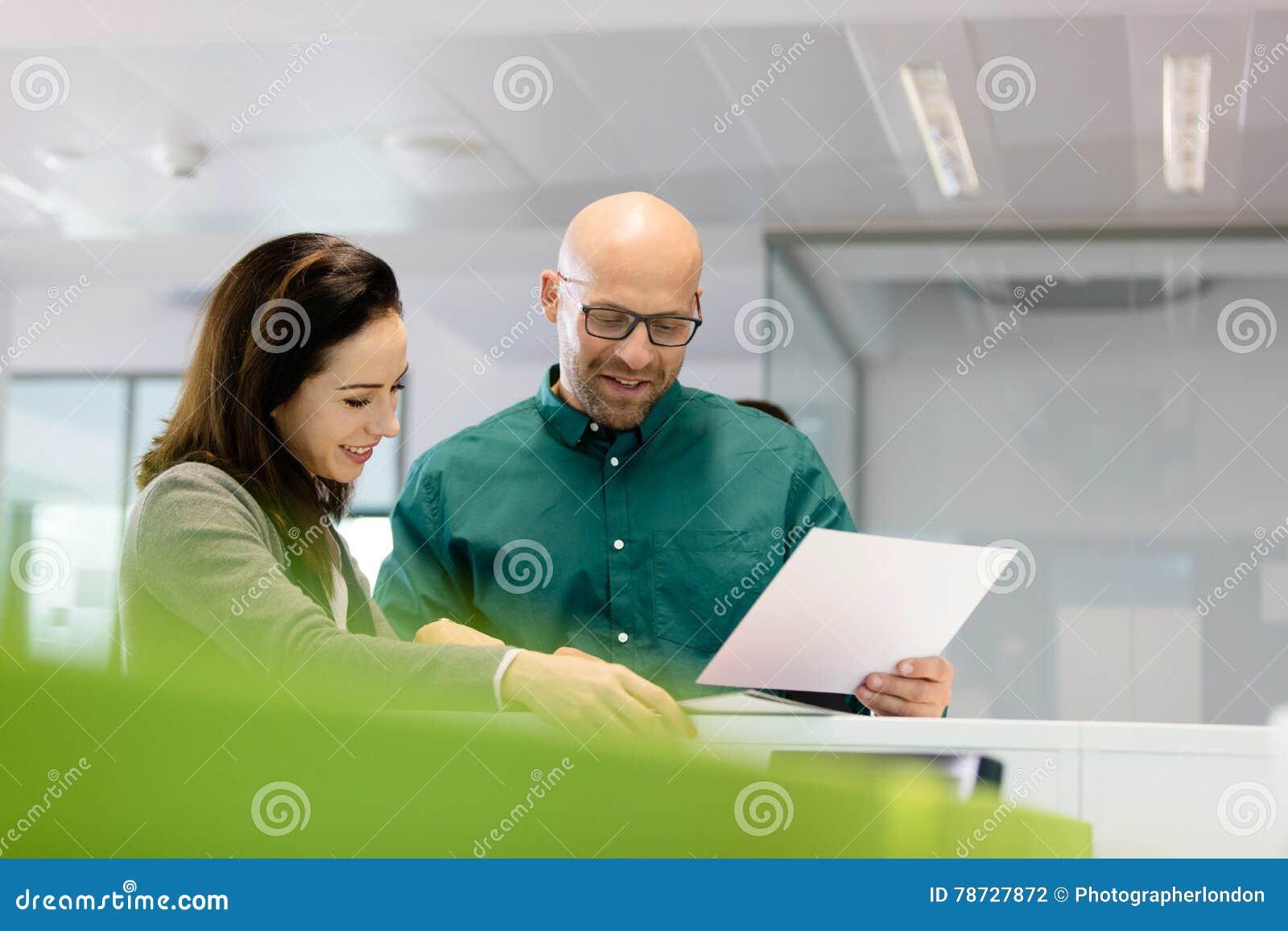 Affärsman och affärskvinna med skrivbordsarbete i regeringsställning
