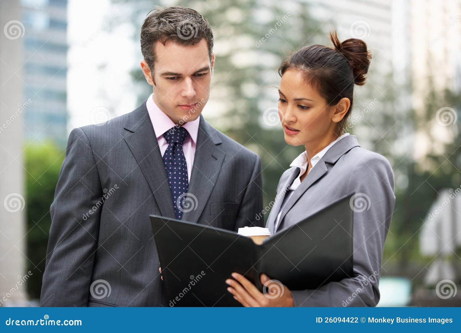 Affärsman och affärskvinna som diskuterar förlagan
