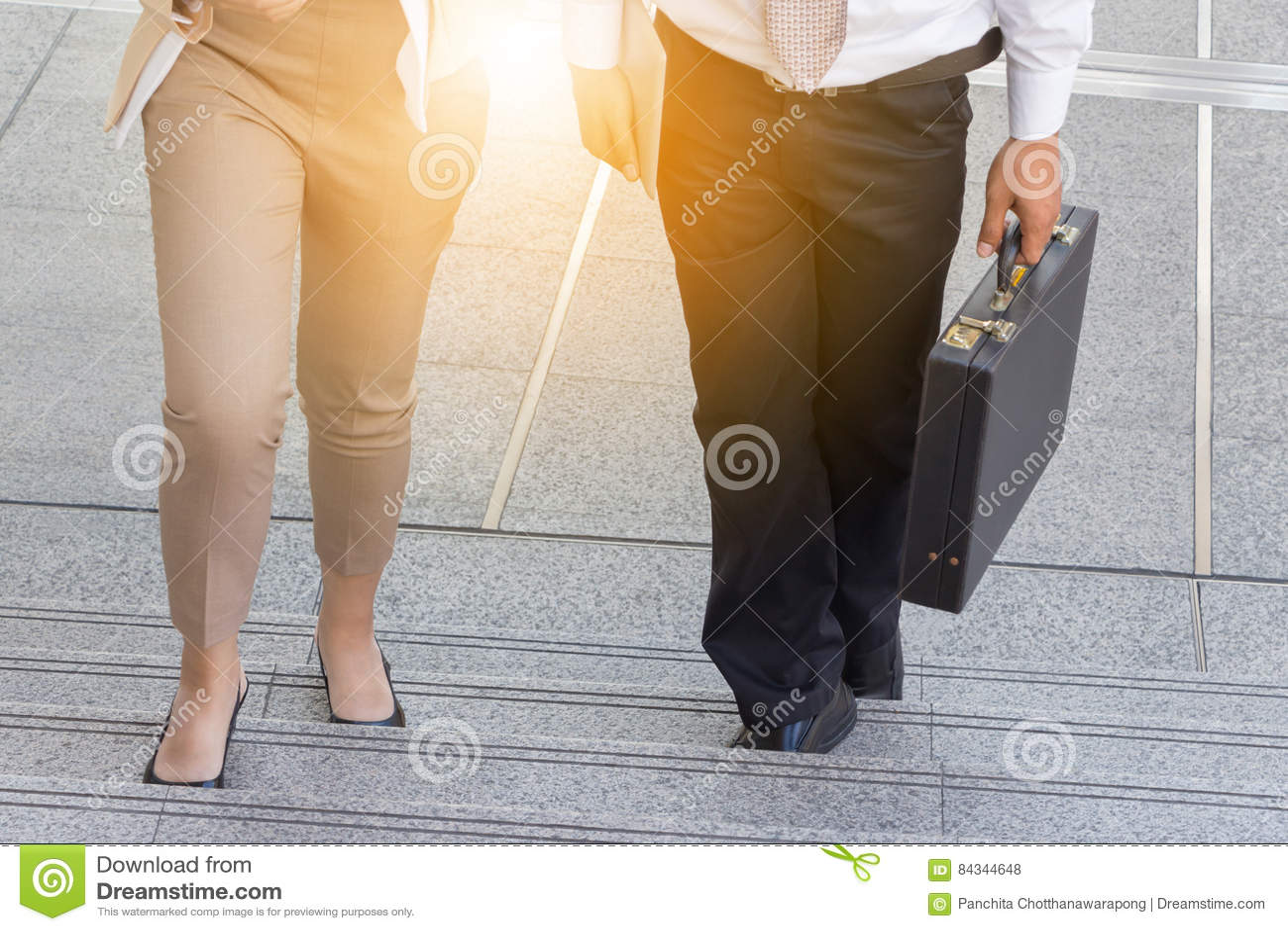 Affärsman- och affärskvinna som går upp trappa med påsar