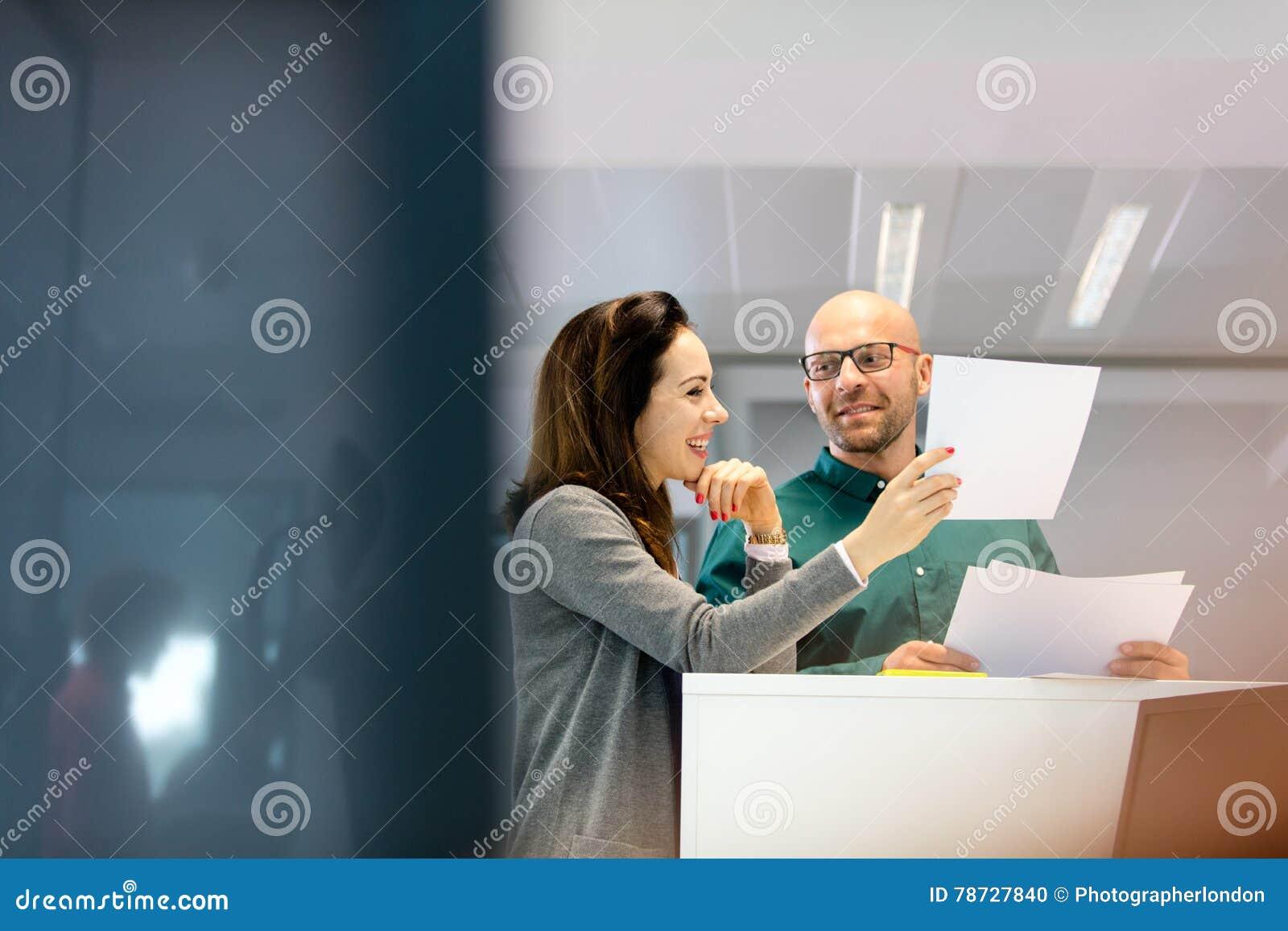 Affärsman och affärskvinna som i regeringsställning diskuterar över dokument