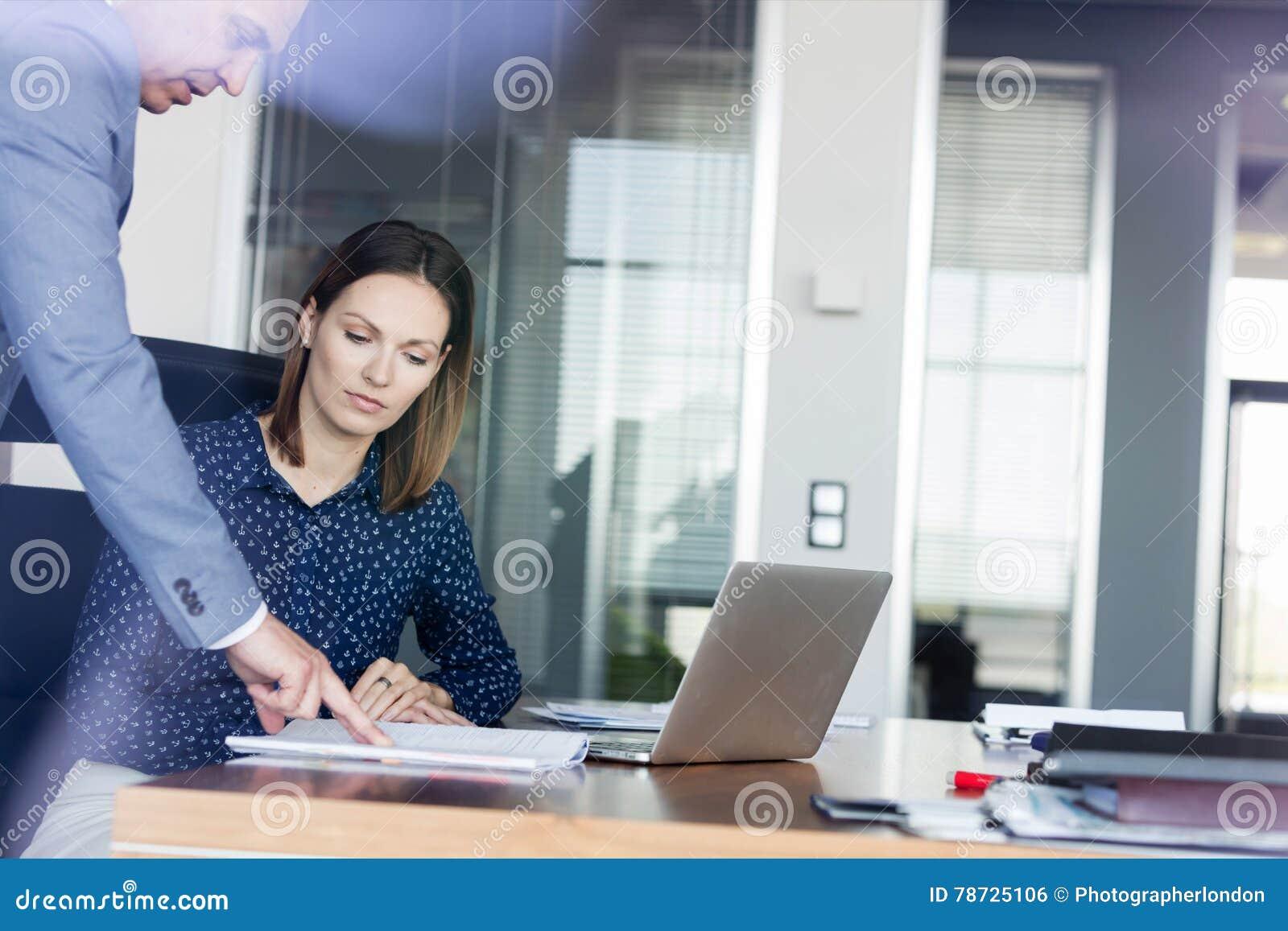 Affärsman och affärskvinna som i regeringsställning diskuterar över dokument på skrivbordet