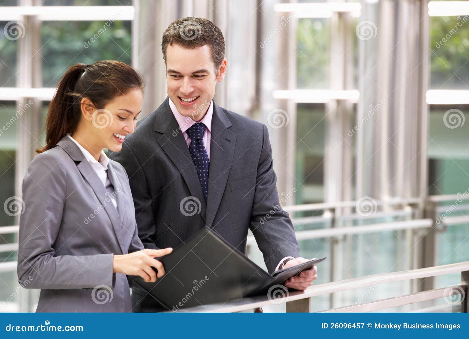 Affärsman och affärskvinna som pratar i gata