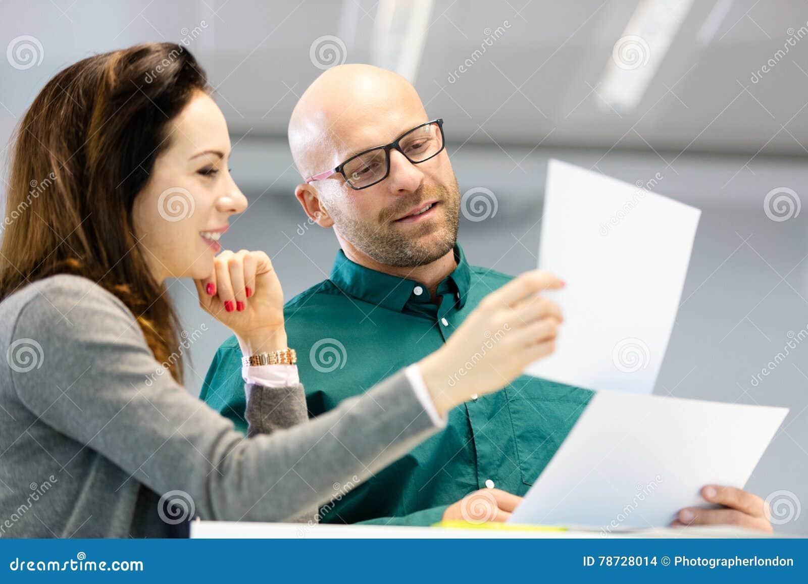 Affärsman- och affärskvinnaläsningdokument i regeringsställning