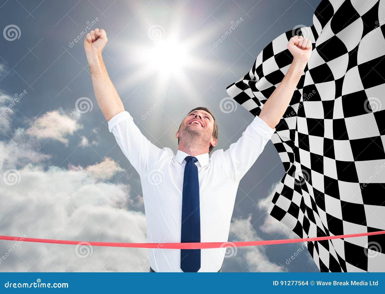 Affärsman på mållinjen mot himmel och rutig flagga