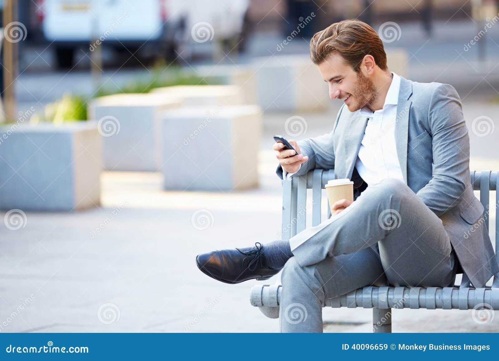 Affärsman On Park Bench med kaffe genom att använda mobiltelefonen