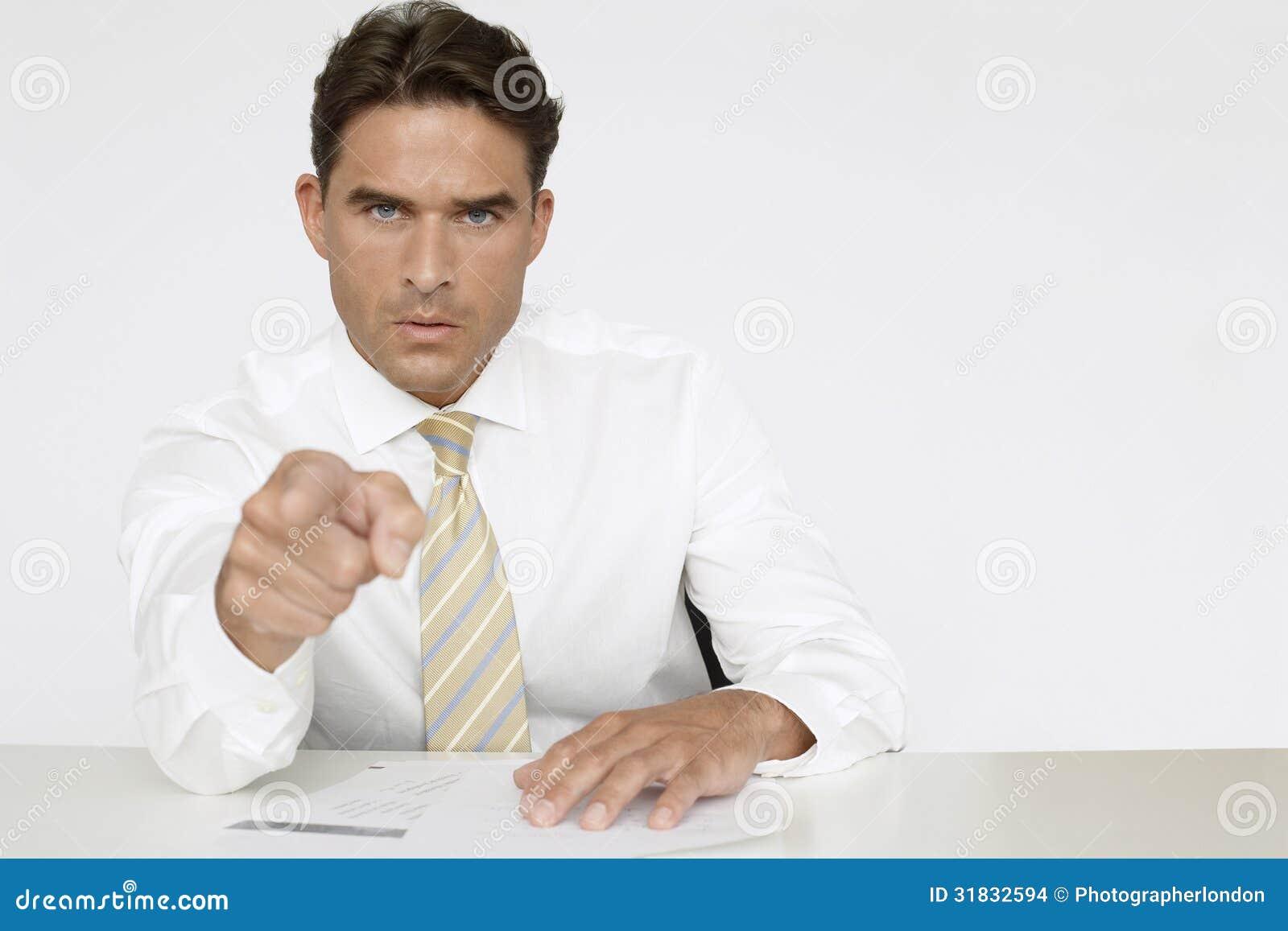 Affärsman Pointing While Sitting på skrivbordet