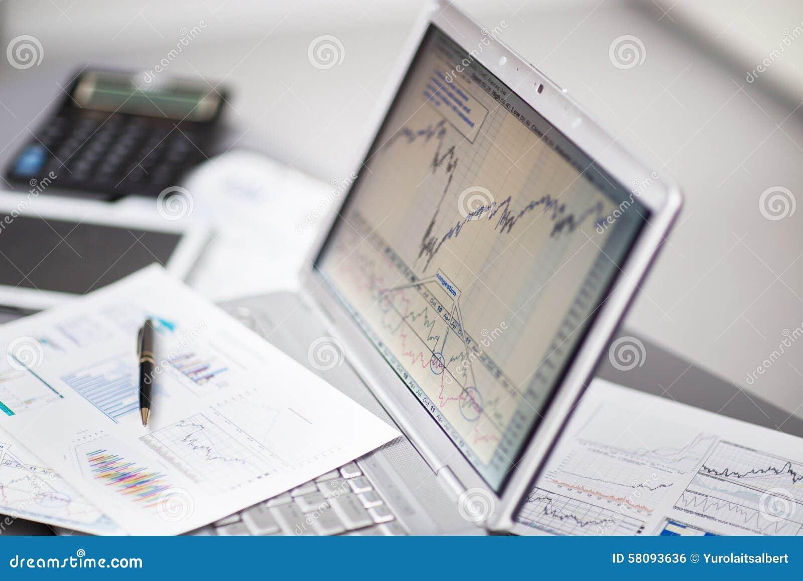 Affärsman som analyserar investeringdiagram med bärbara datorn