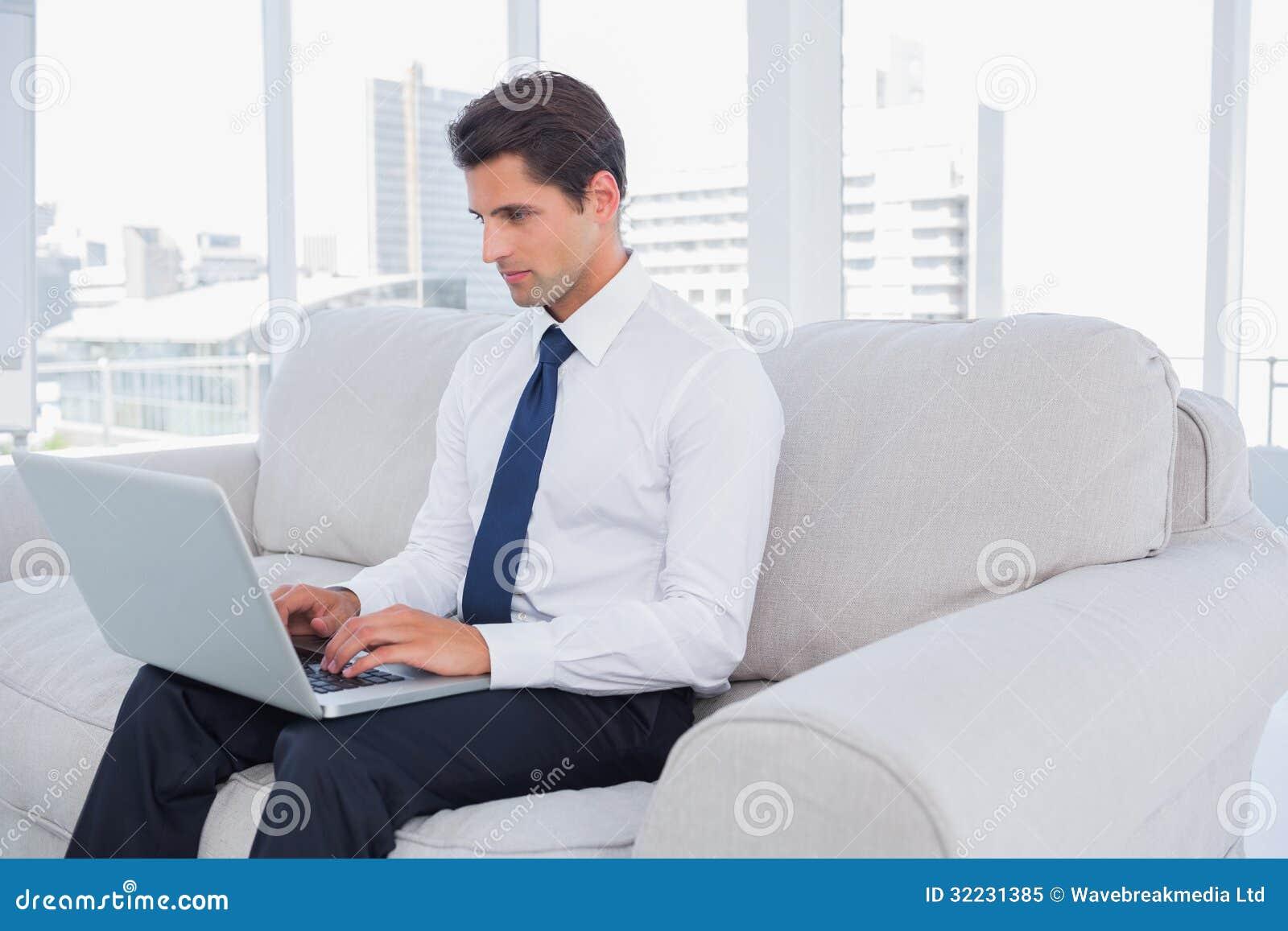 Affärsman som använder bärbara datorn på en soffa