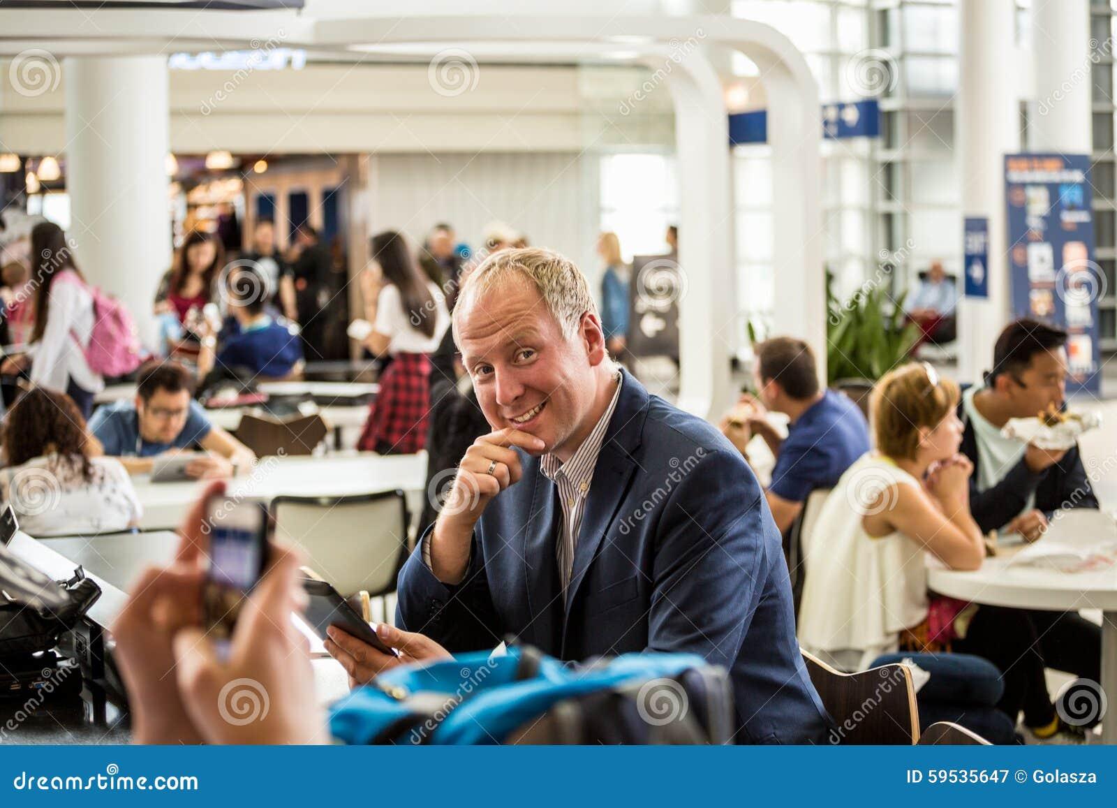 Affärsman som använder hans minnestavla på flygplatsen