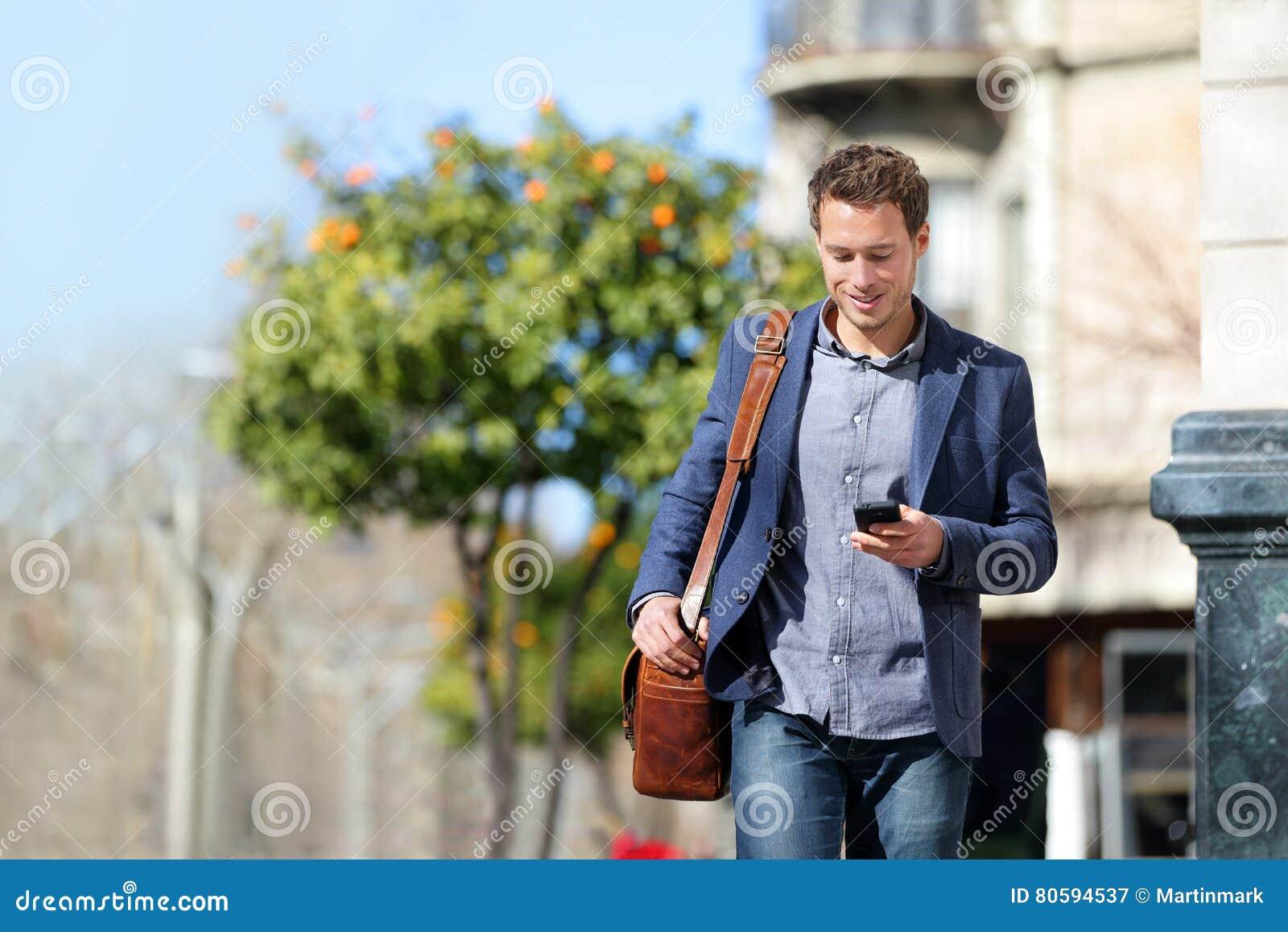 Affärsman som använder mobiltelefonen som går för att arbeta