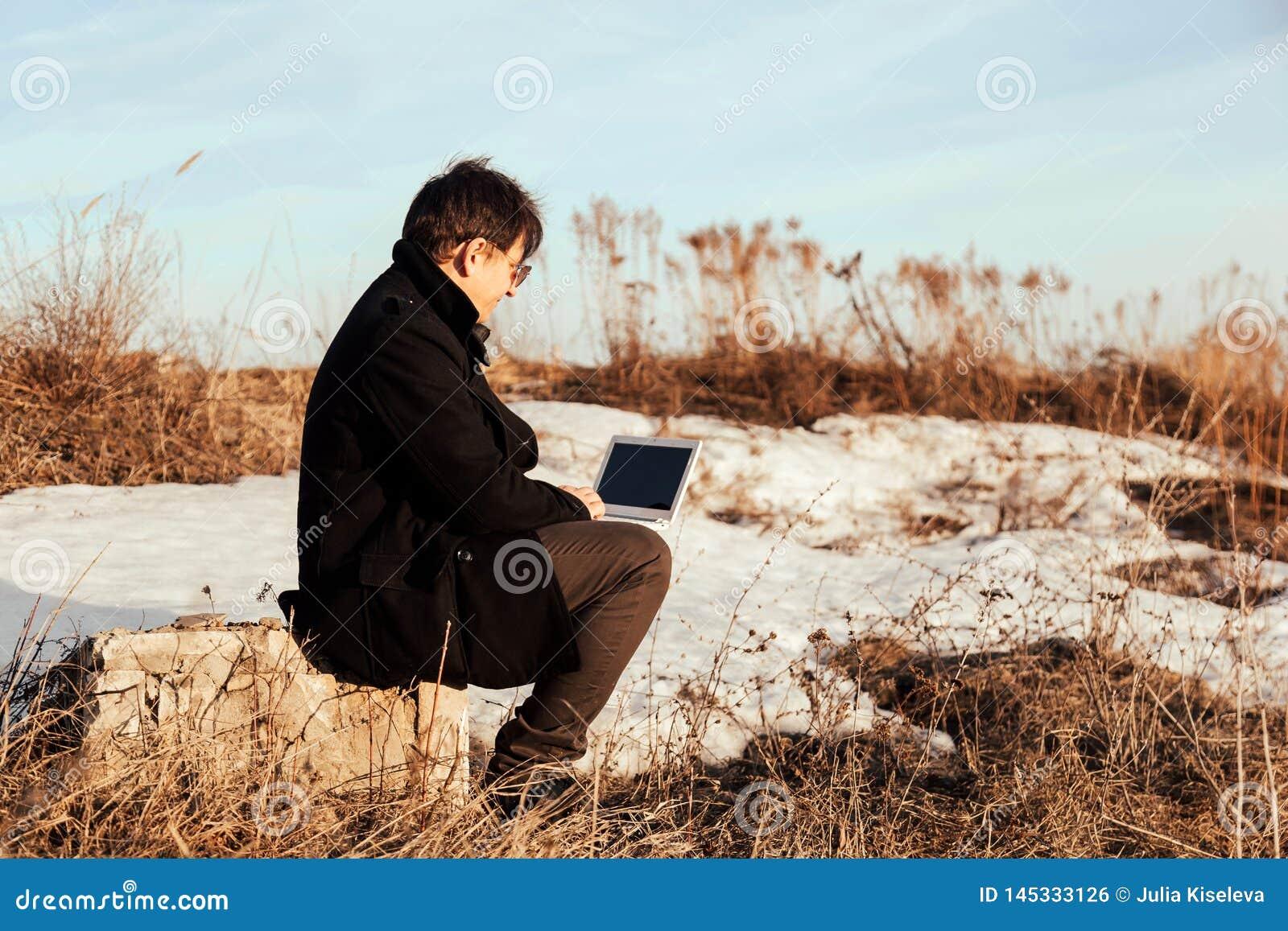 Affärsman som arbetar med hans bärbar dator utanför