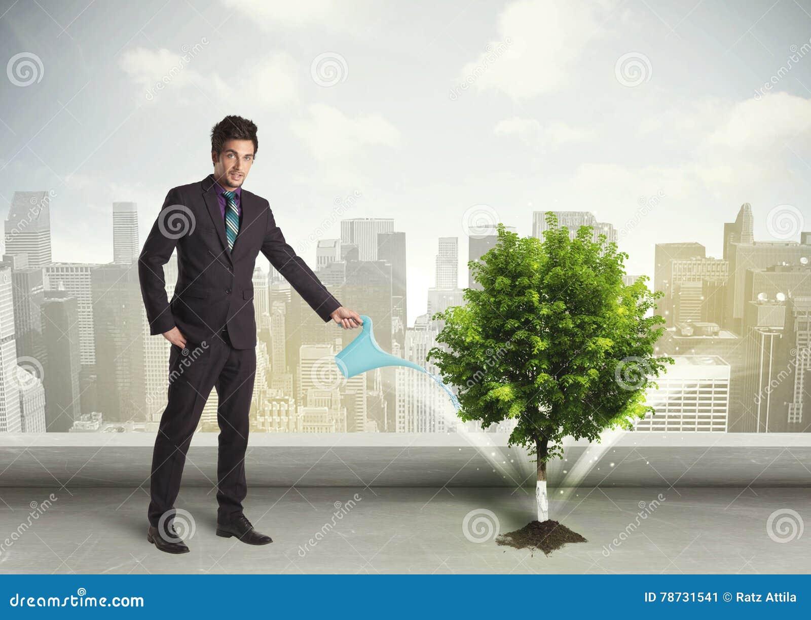 Affärsman som bevattnar det gröna trädet på stadsbakgrund