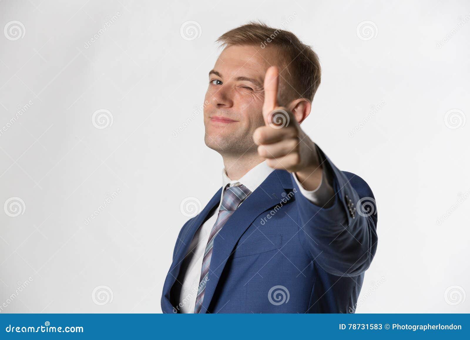 Affärsman som blinkar och pekar till kameran