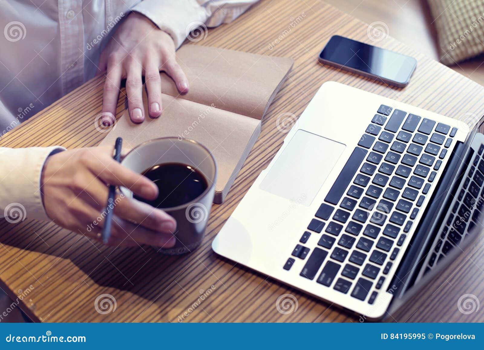 Affärsman som dricker kaffe och arbete på bärbar datordatoren, mobiltelefon, handstilaffärsplan, bärande vit skjorta