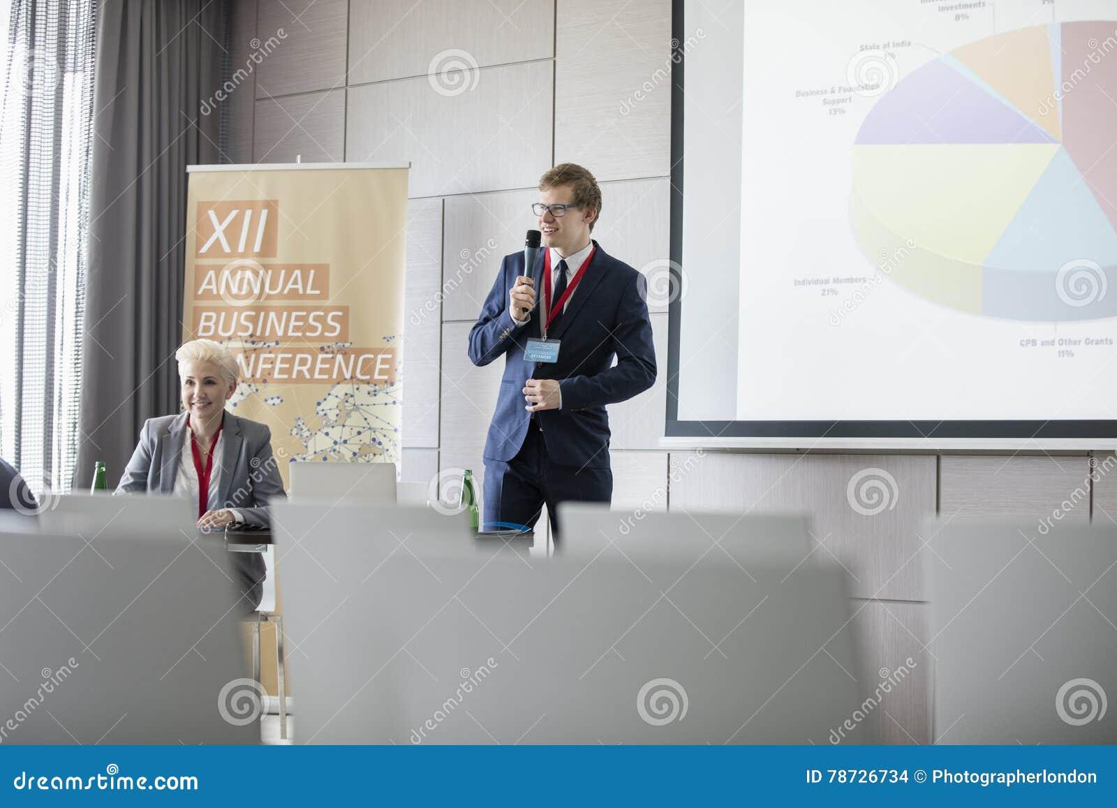 Affärsman som förklarar pajdiagrammet i seminariumkorridor