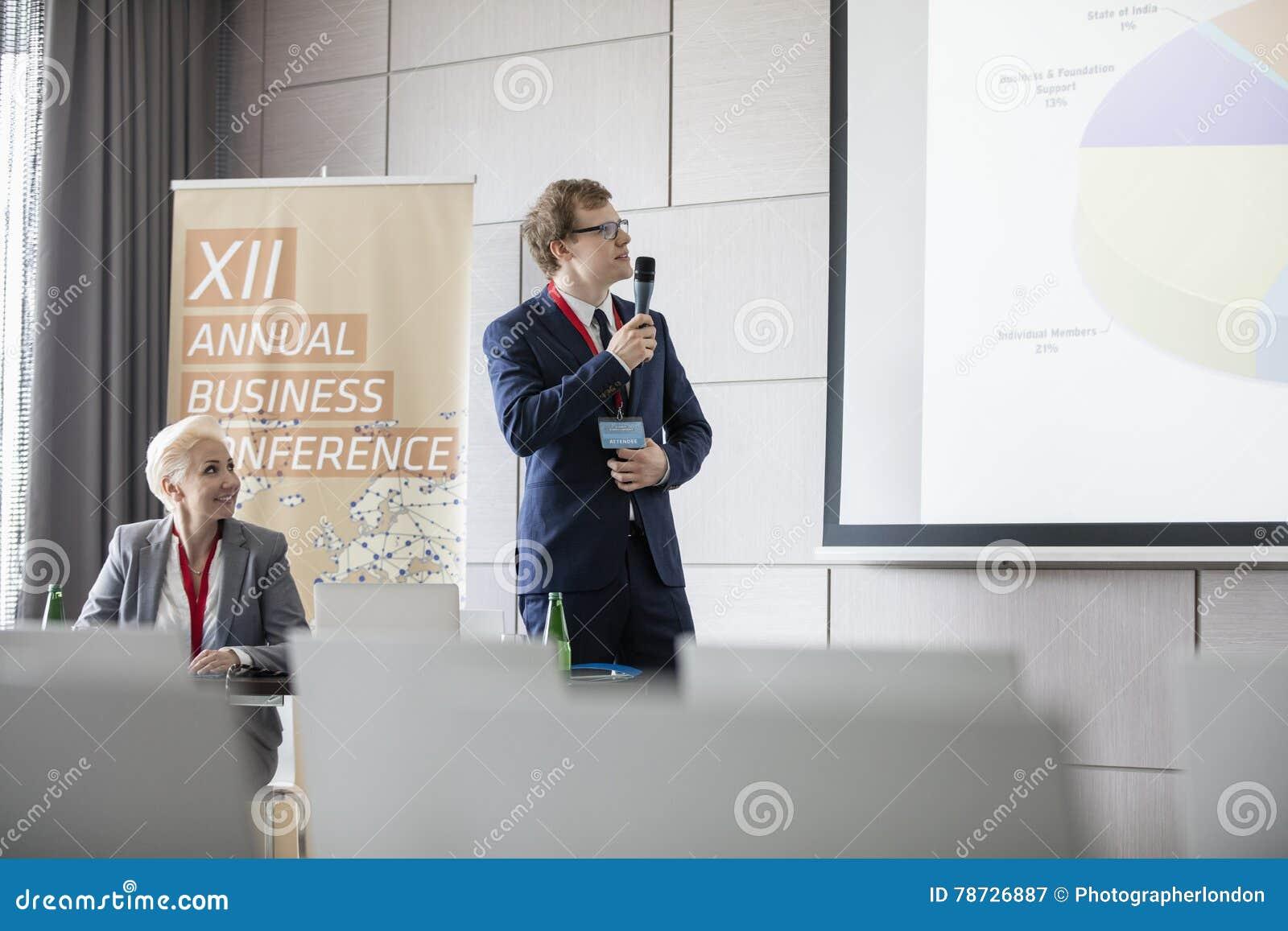 Affärsman som förklarar pajdiagrammet i seminariumkorridor i konventcentrum