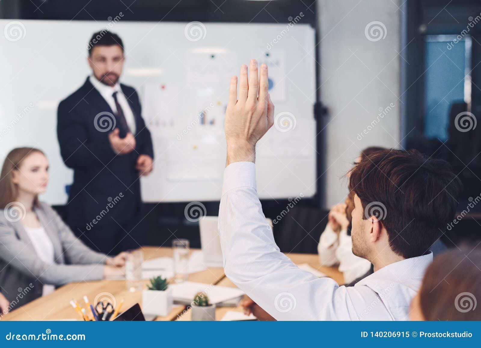 Affärsman som frågar fråga till högtalaren på presentationen