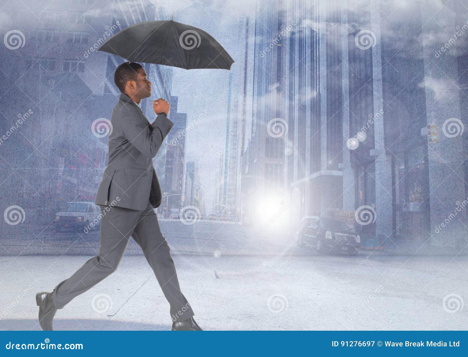 Affärsman som går med paraplyet i stad