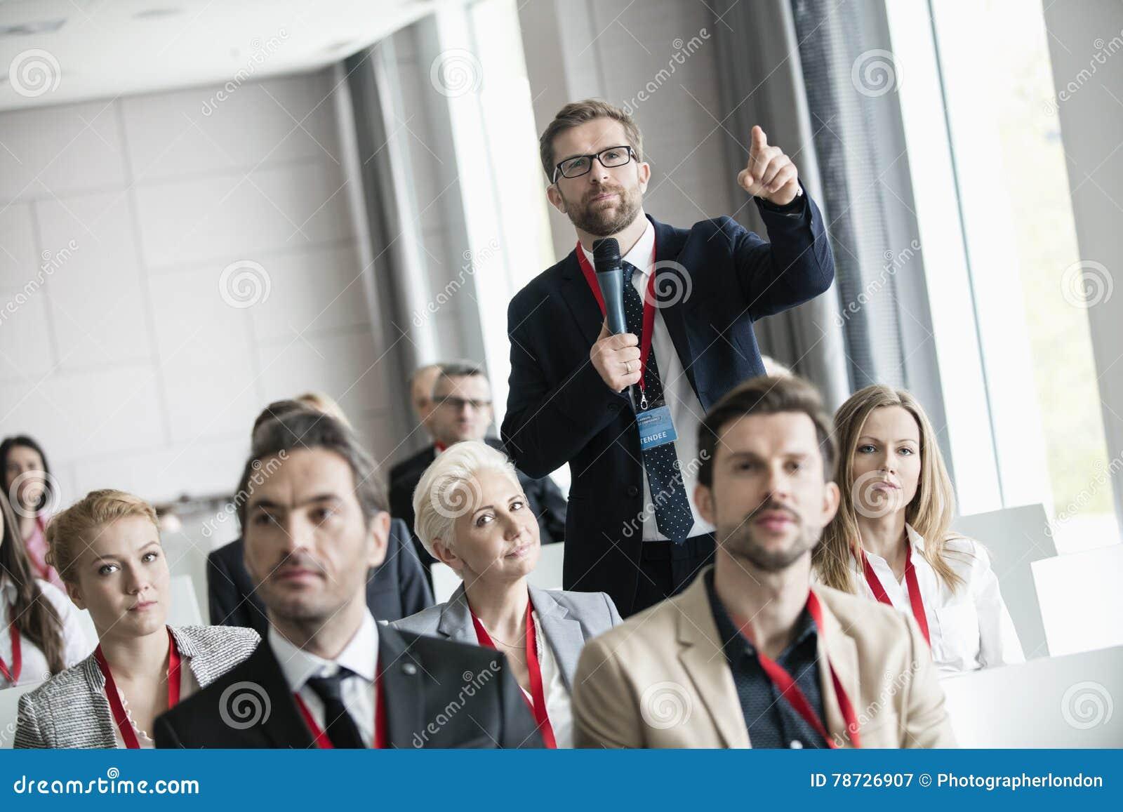 Affärsman som gör en gest, medan fråga fråga under seminarium i konventcentrum