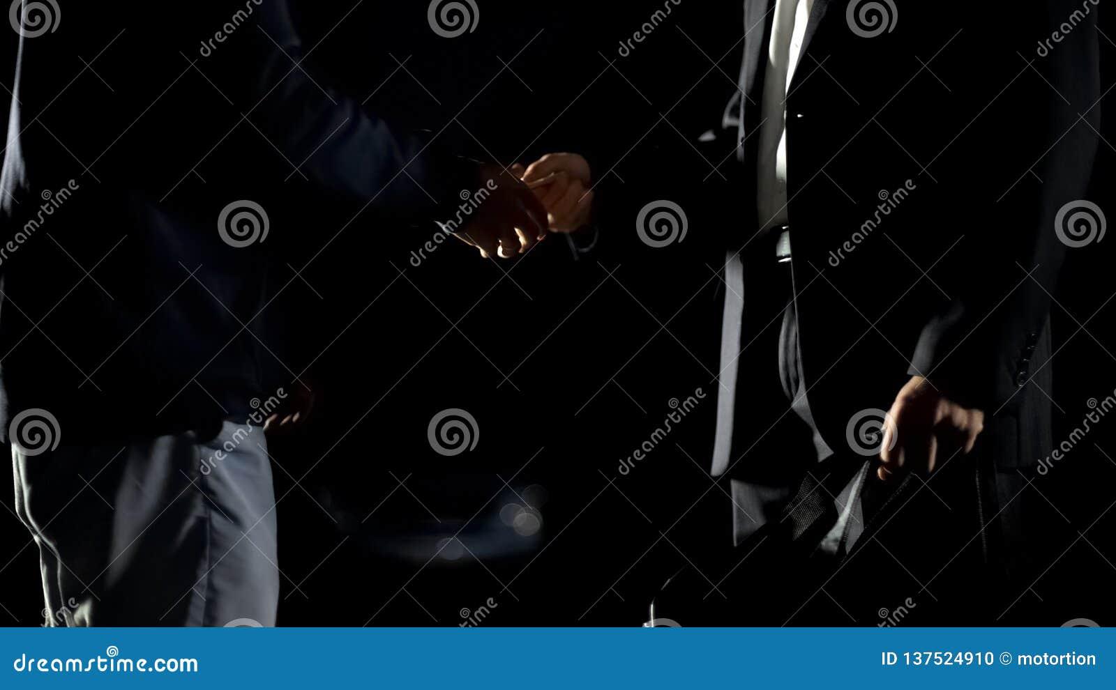 Affärsman som ger kassa till återförsäljaren som rymmer den stort påsen, droger eller trafikera för vapen
