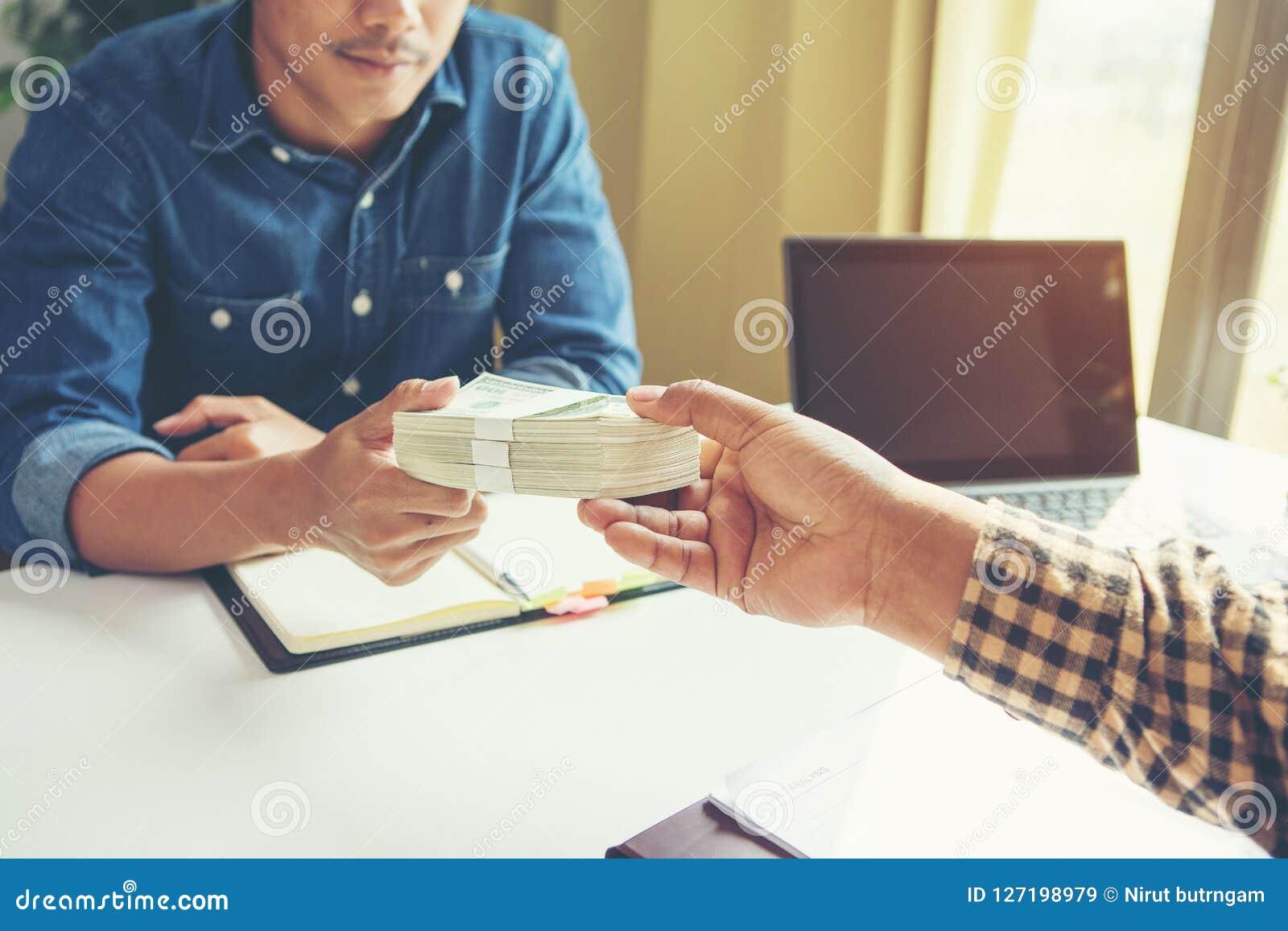 Affärsman som ger pengar till hans partner, medan göra avtalet -