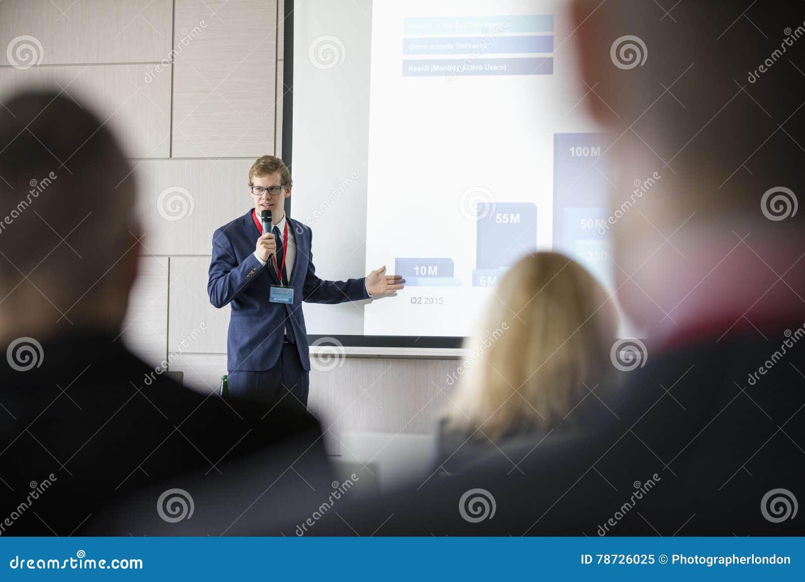 Affärsman som ger presentation i seminariumkorridor på konventcentret